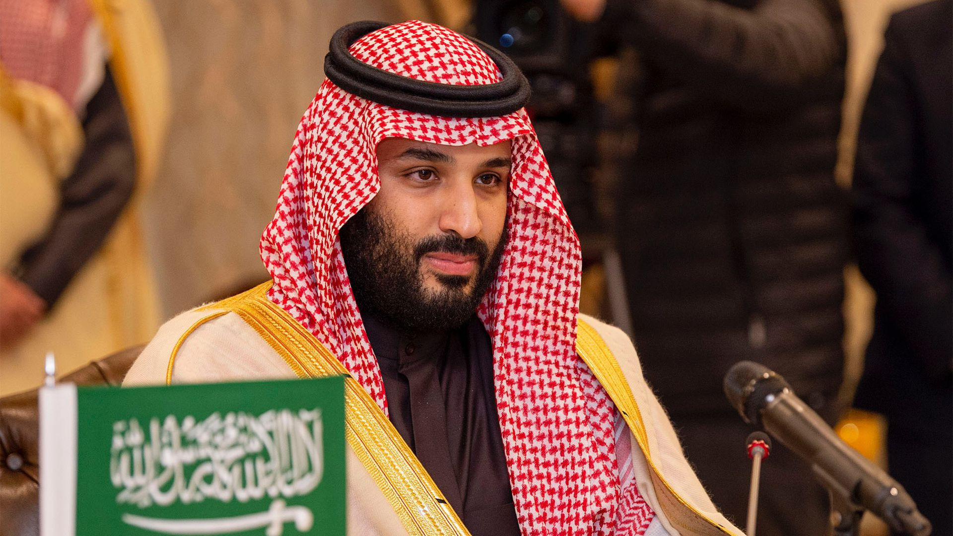 In this image, Crown Prince of Saudi Arabia Mohammad bin Salman sits behind a small green and white Saudi Arabian flag.