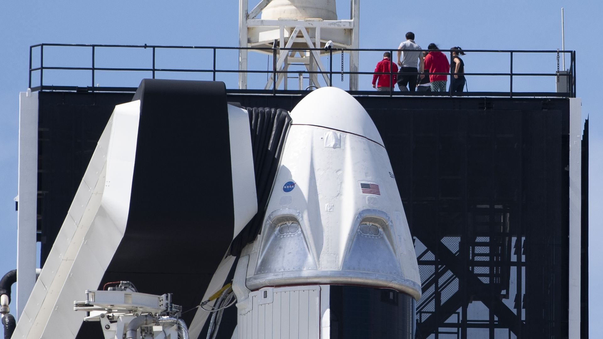 The SpaceX Falcon 9 rocket with the unmanned Crew Dragon capsule on its nose sits at Kennedy Space Center in Florida.