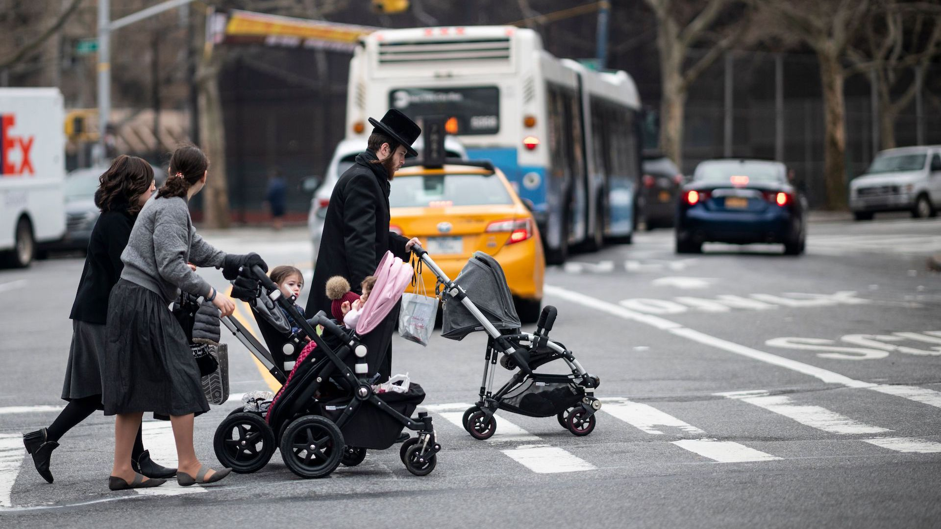 Orthodox Jewish parents push children in strollers in Williamsburg, Brooklyn, where a measles outbreak is underway