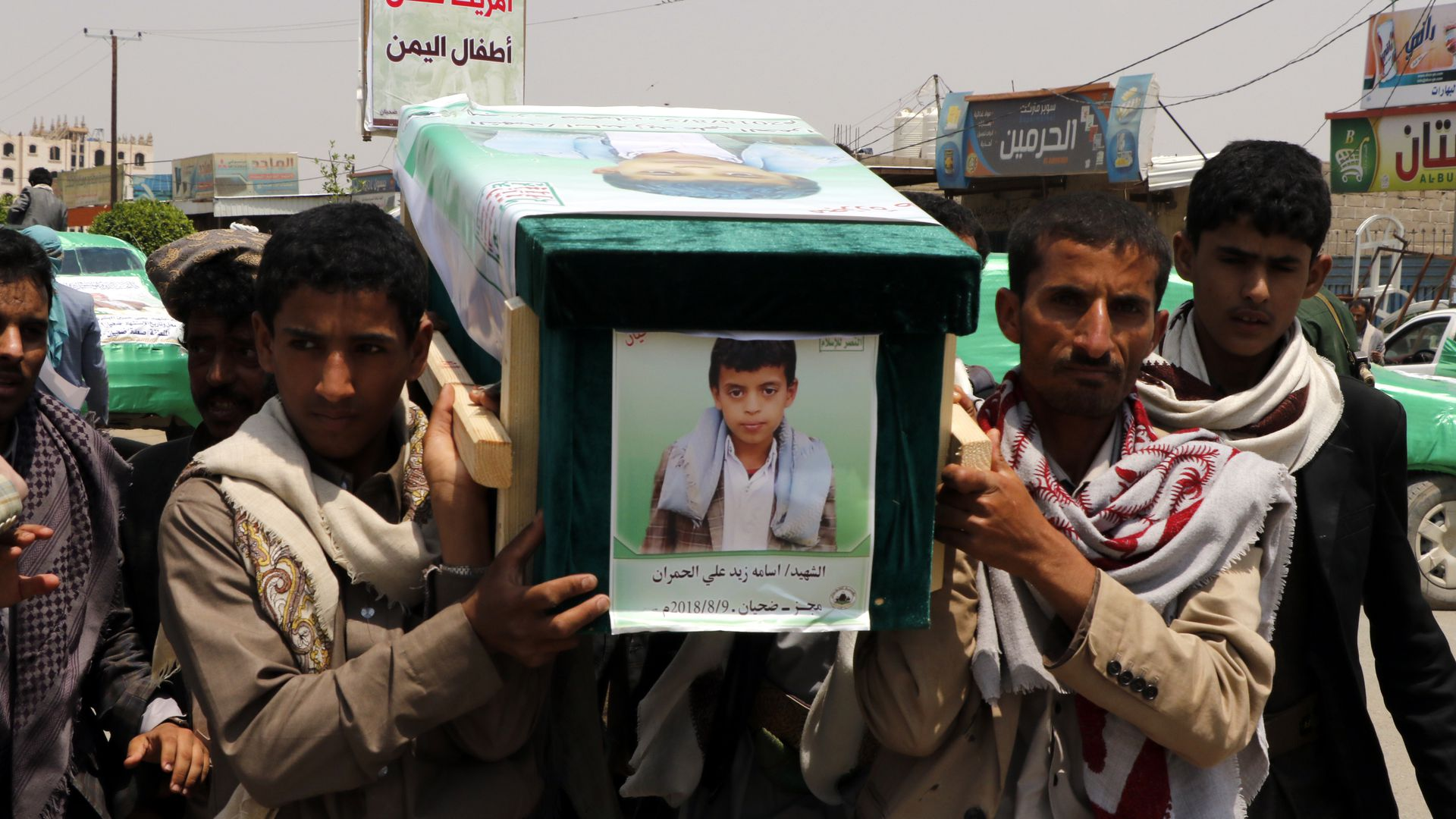 Mourners carry the coffin of a child.