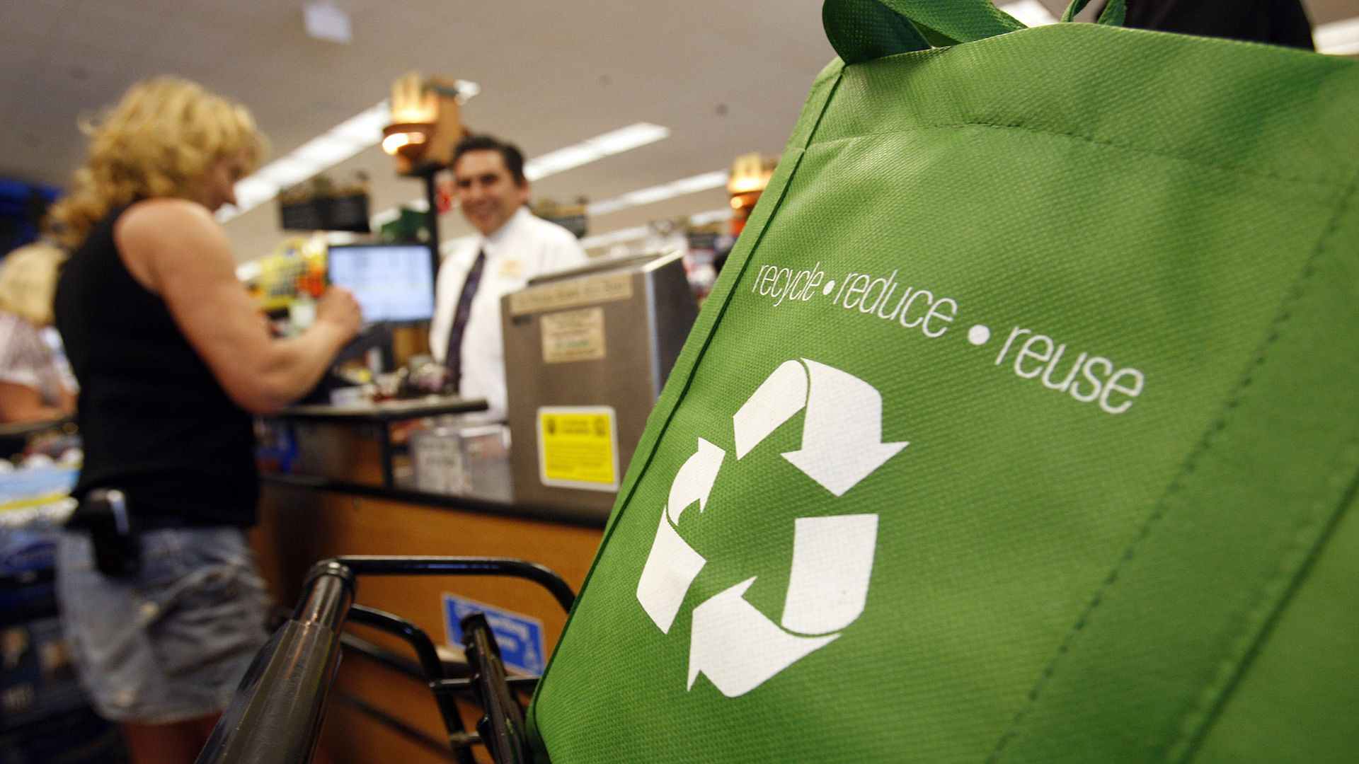 Woman checks out in grocery store in background, with reduce recycle reuse green bag in front.