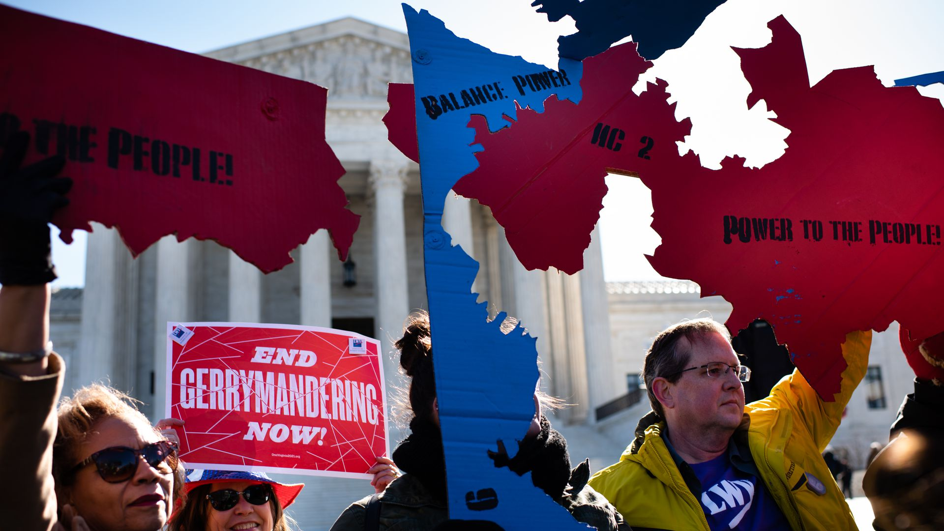 """In this image, people in coats hold up signs that read """"End Gerrymandering now"""" and """"power to the people"""" while standing in front of the Supreme Court."""