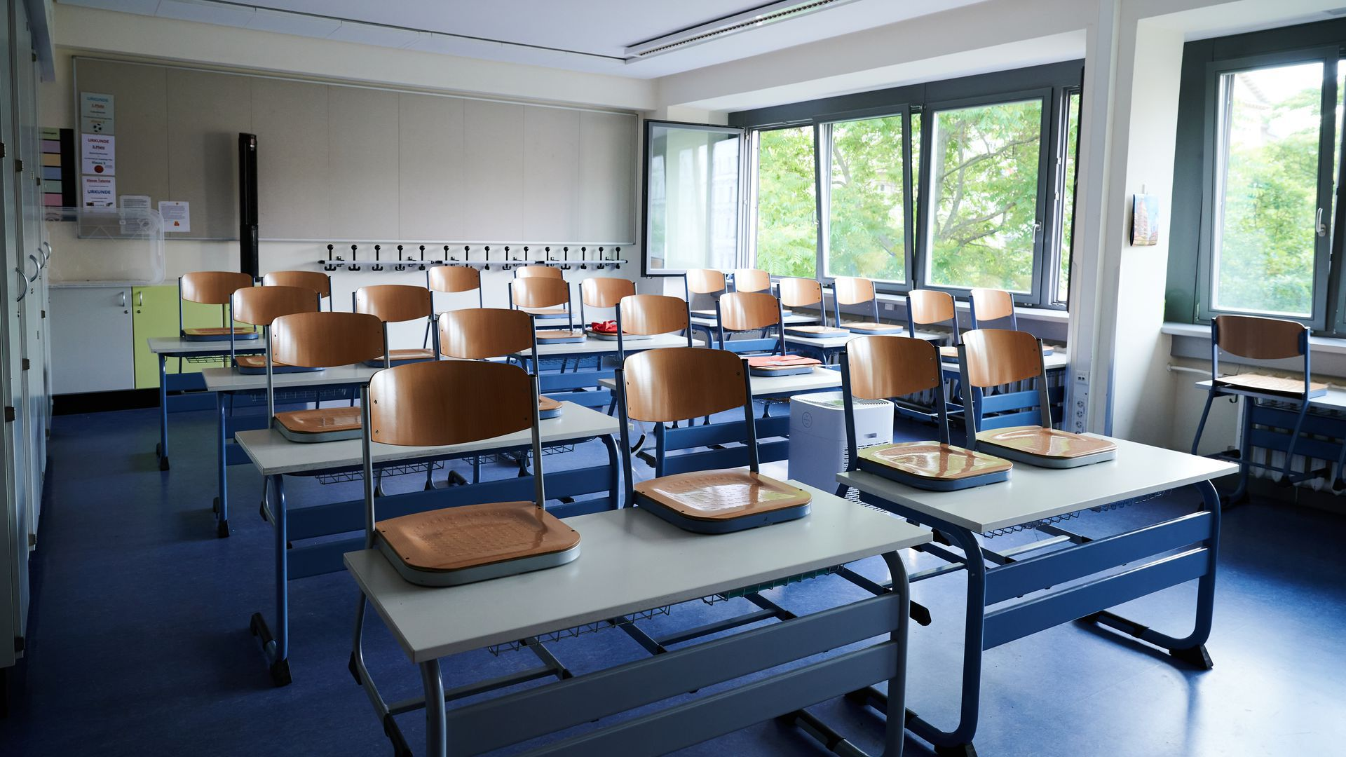 Empty school desks and chairs stacked on top in a classroom.