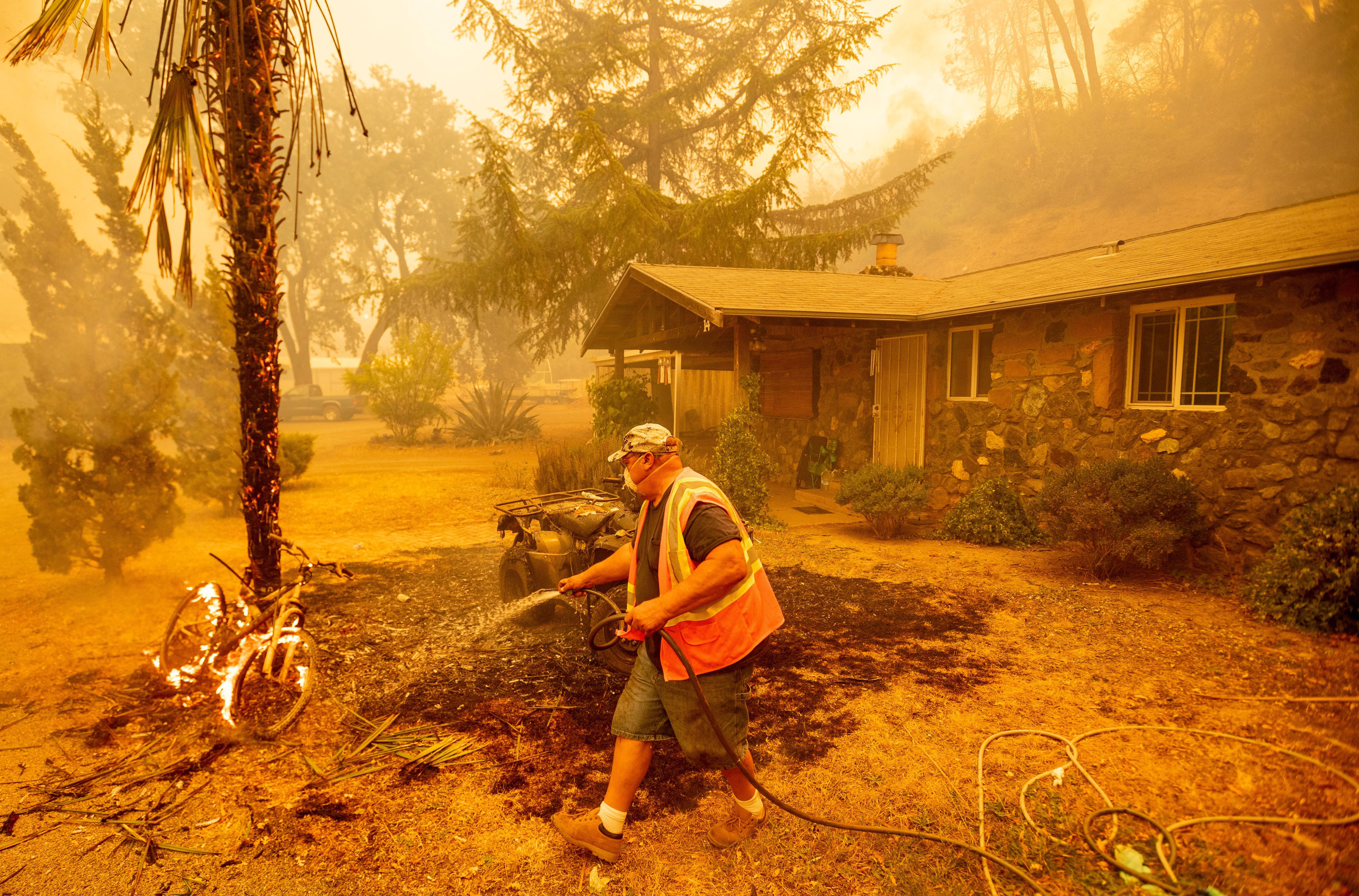 A resident hoses down a burning bicycle and tree as flames from the Hennessey approach a property in the Spanish Flat area of Napa, California on Aug. 18.