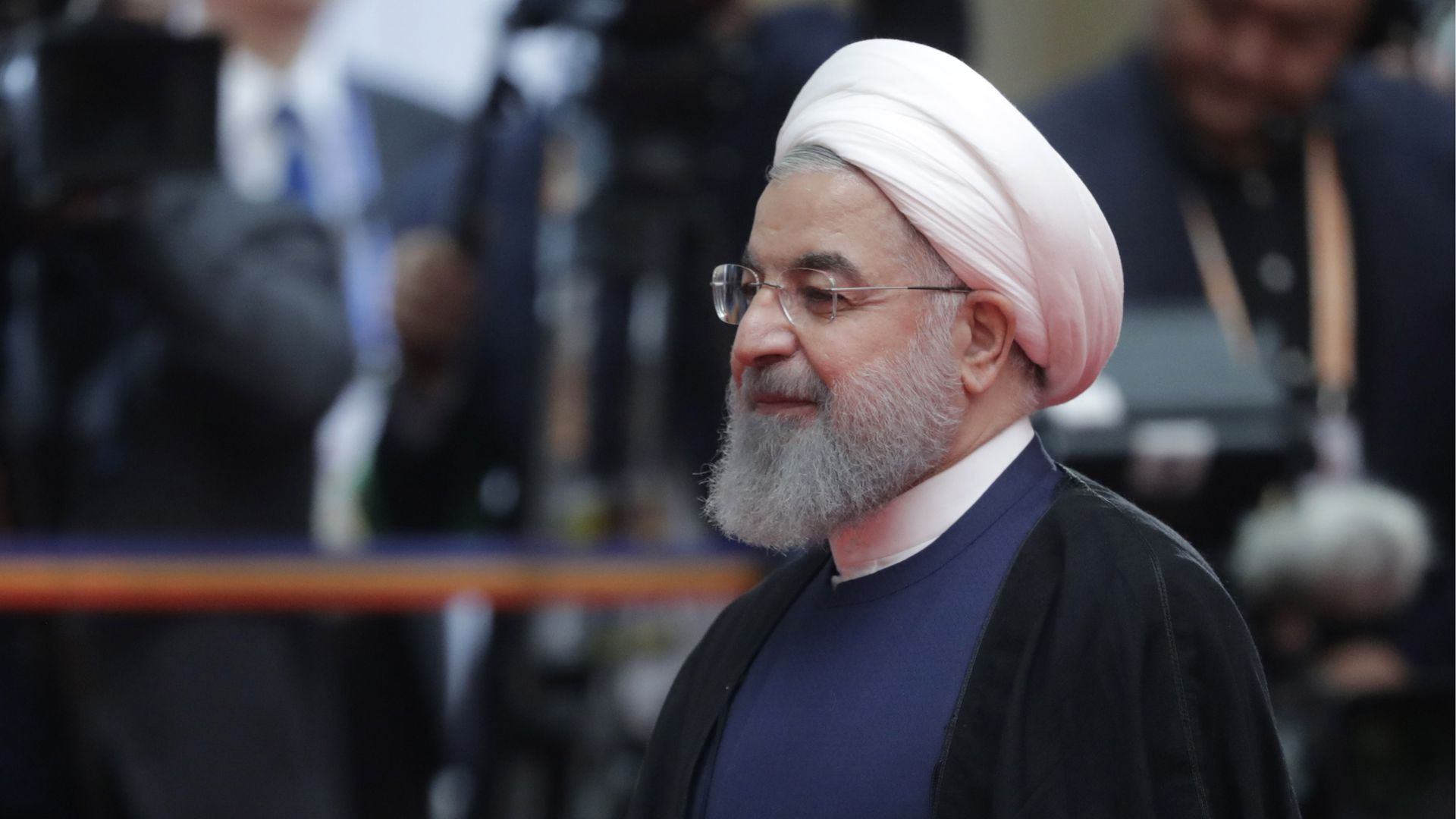 Iranian President Hassan Rouhani walks by photographers