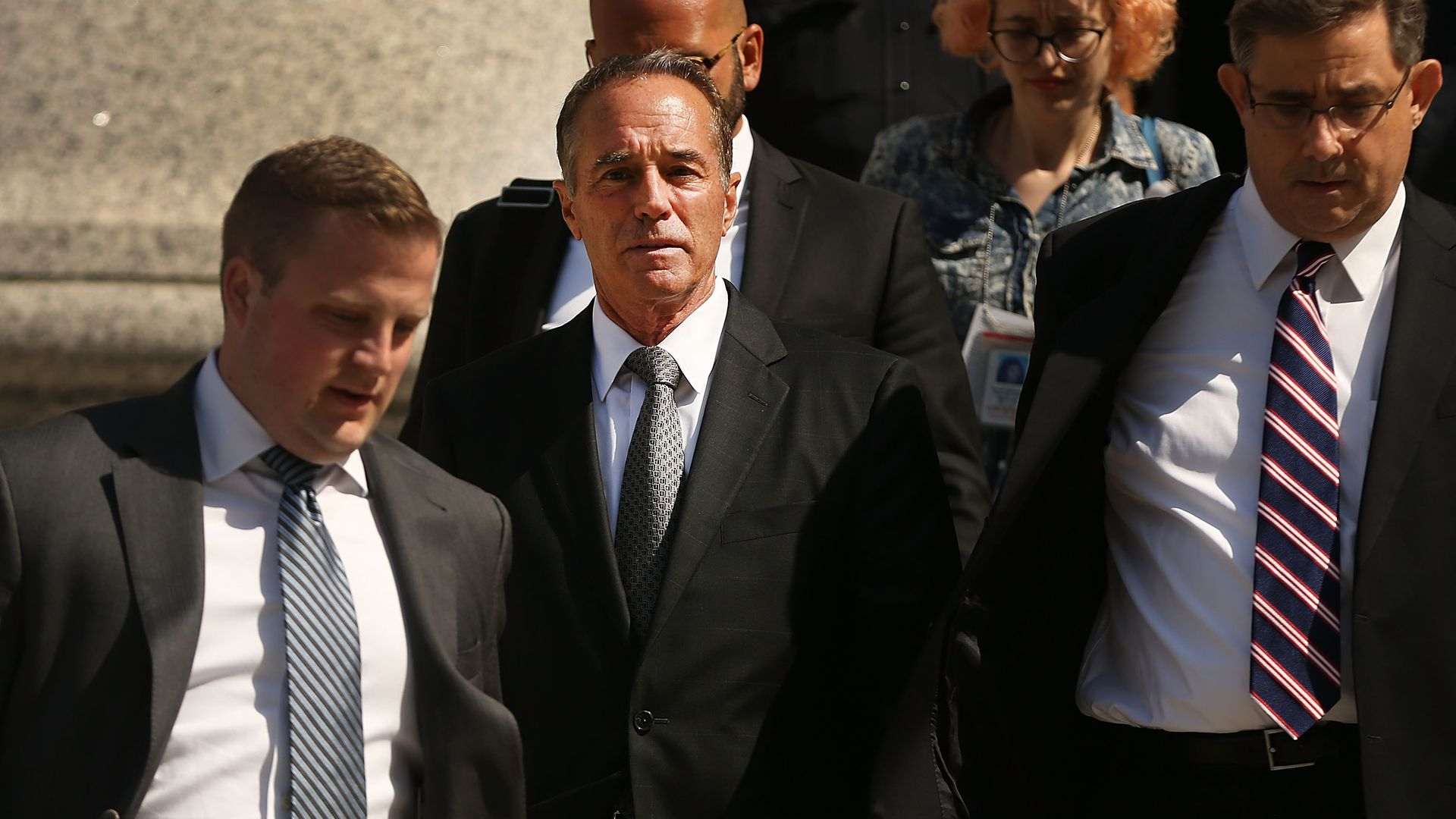 Rep. Chris Collins walking out of a court house surrounded by body guards