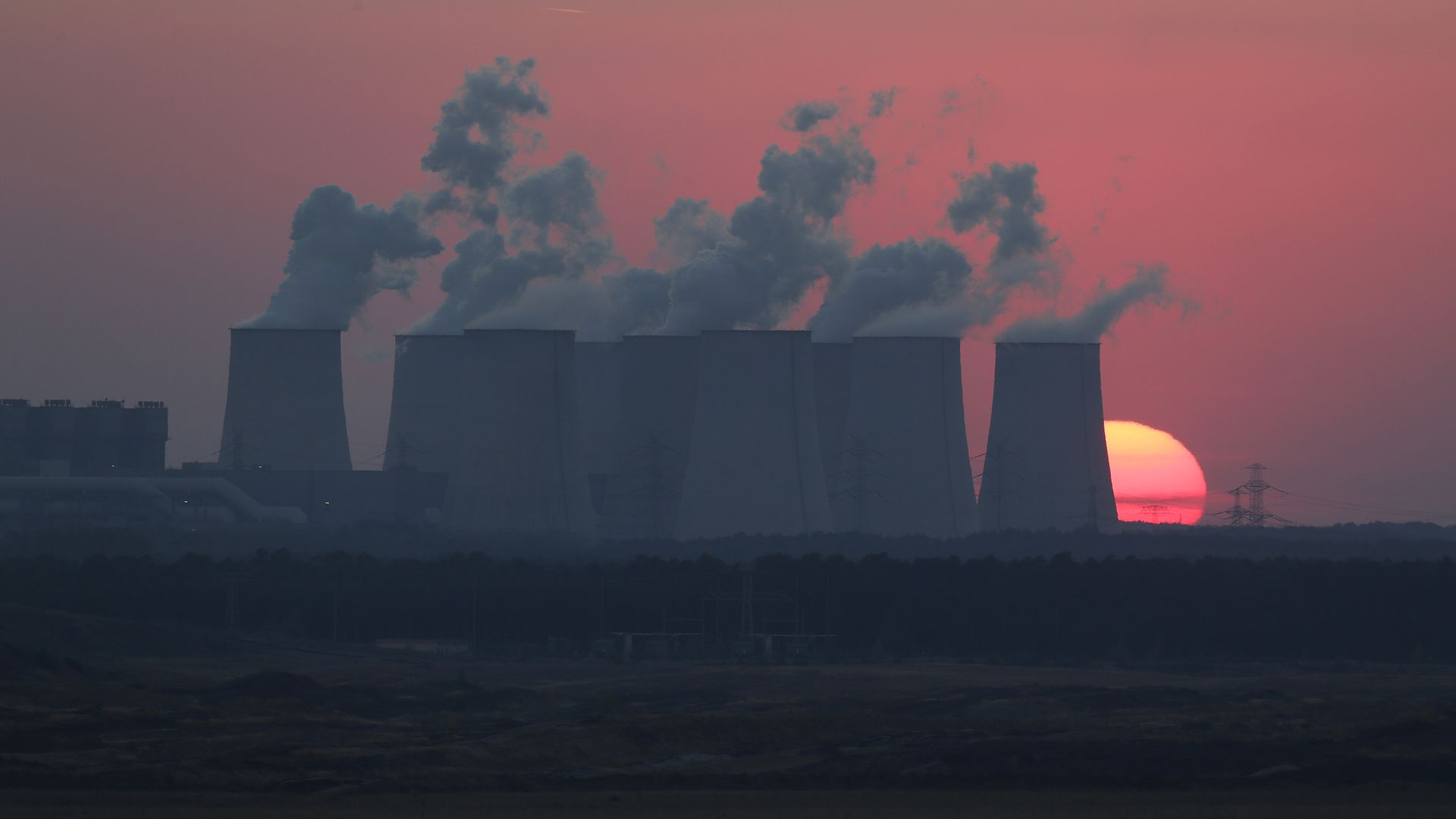 A power plant producing lots of smoke in front of a beautiful, red sunset