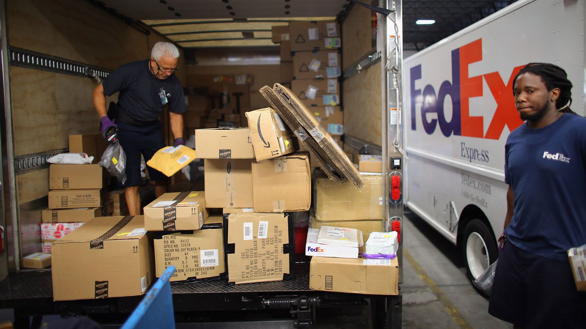 Fedex workers loading packages into a truck