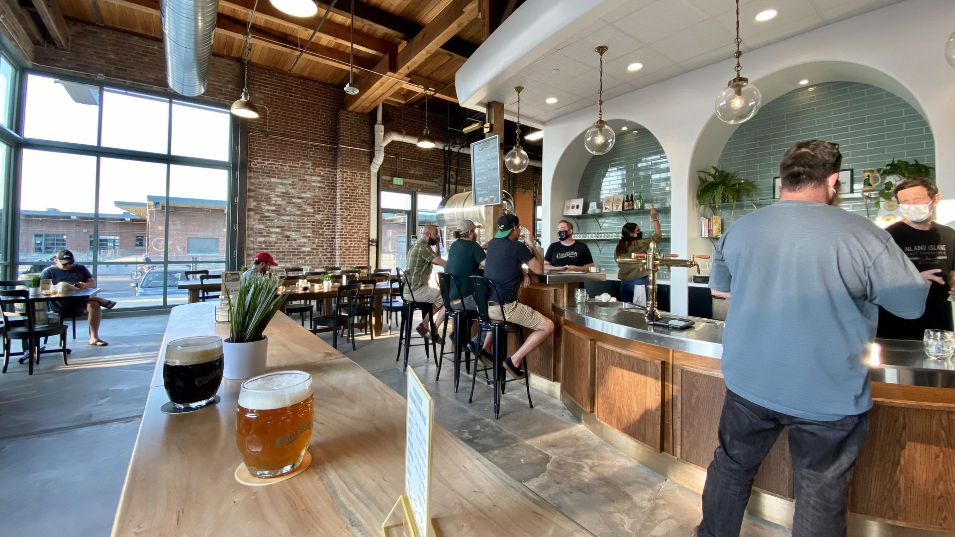 Two beers sit on a table at a Denver brewery with customers drinking in the background.