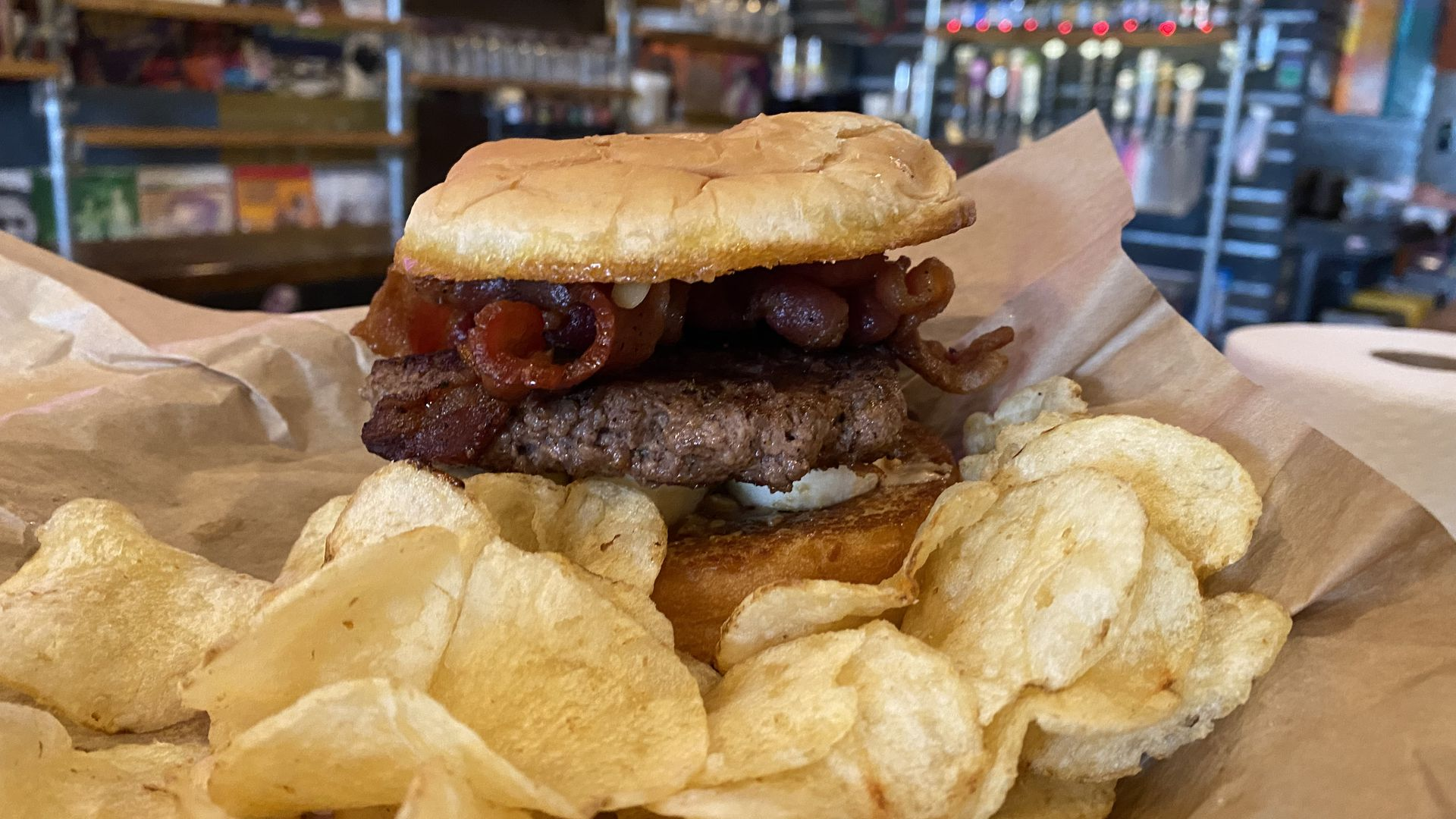 A photo of a burger with a side of potato chips.