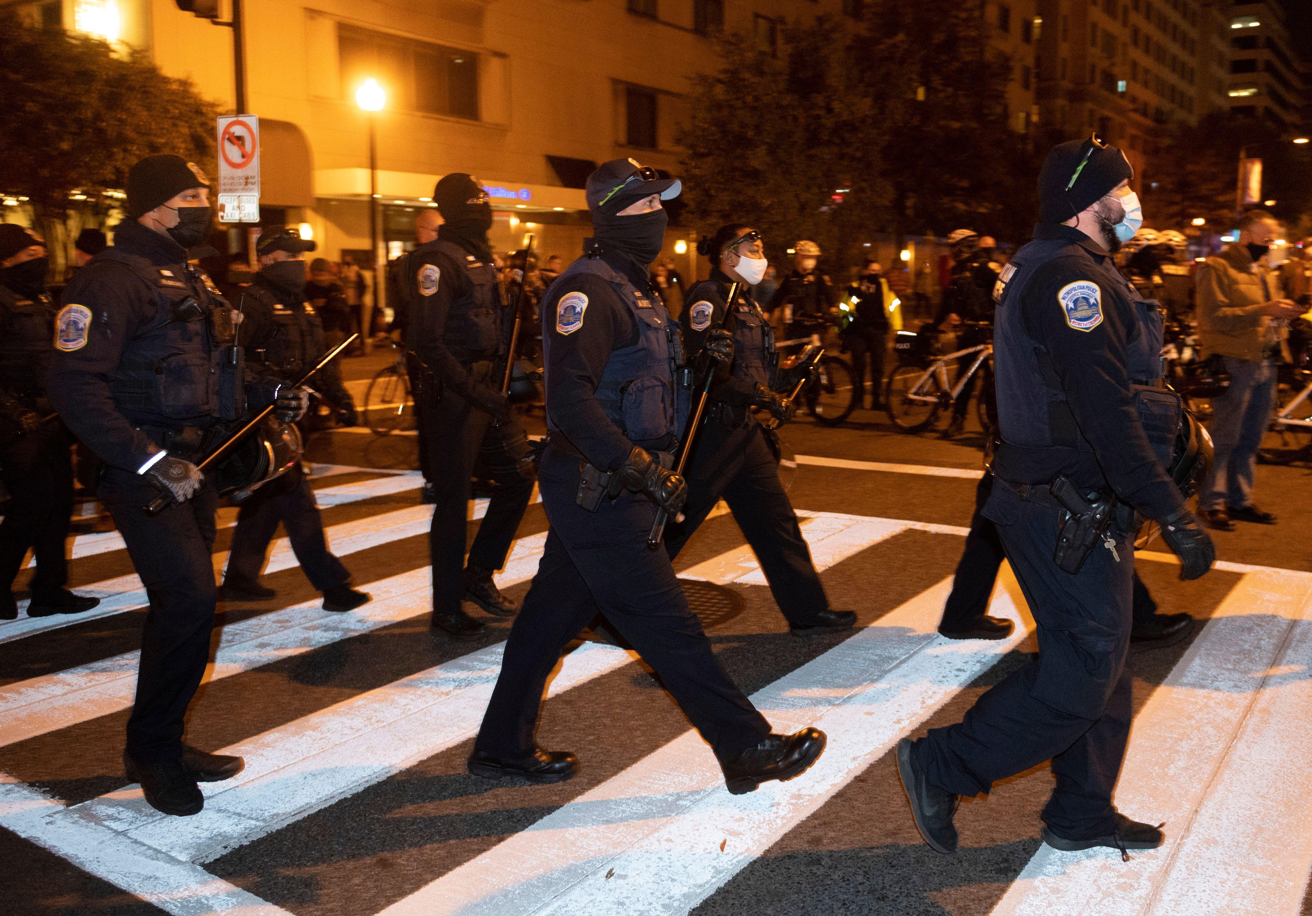 La police marche pour bloquer les contre-manifestants au Black Lives Matter Plaza après le rassemblement des partisans pro-Trump à Washington, DC, le 14 novembre
