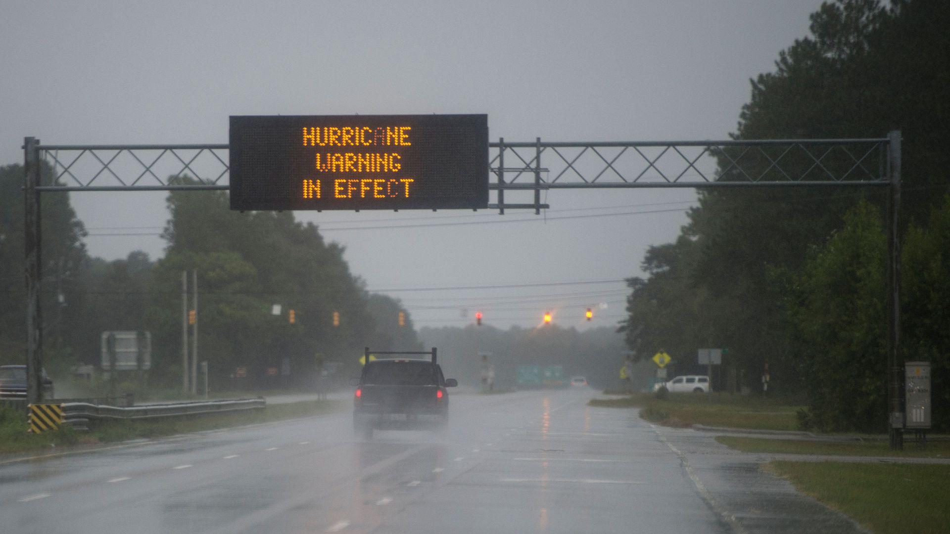 Hurricane warning in effect sign hangs above rainy street