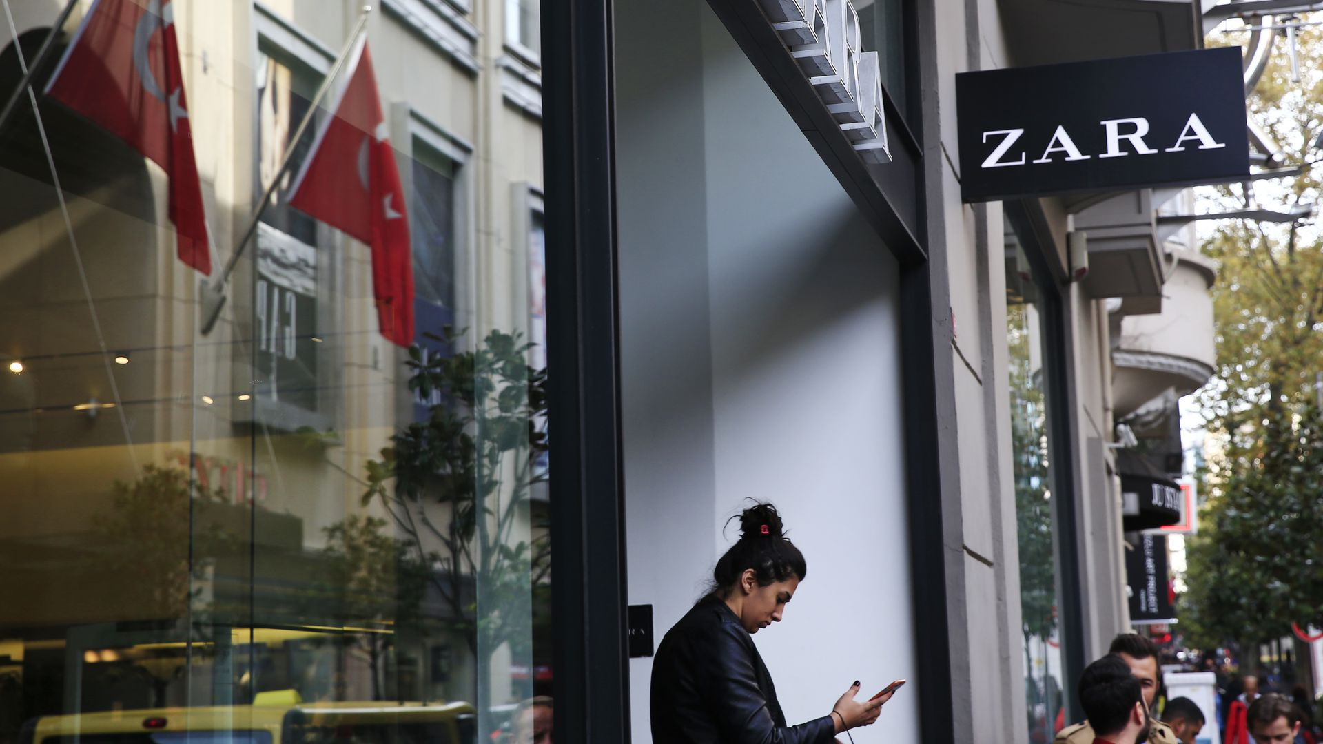 Photo of women gazing at cellphone in front of Zara store in an upscale Istanbul neighborhood