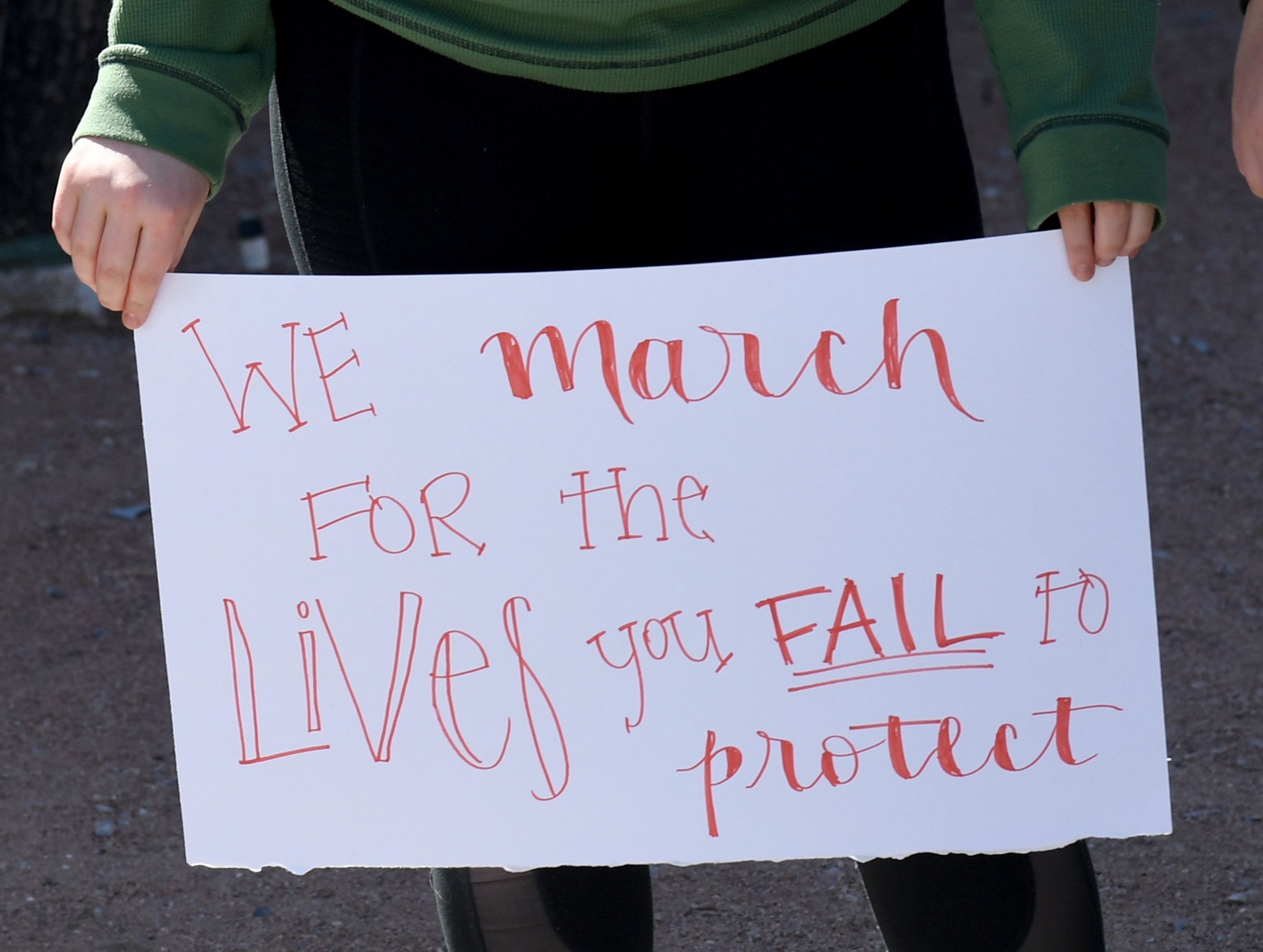Palo Verde High School student Mallory McKissick holds a sign outside the school as she participates in the National School Walkout