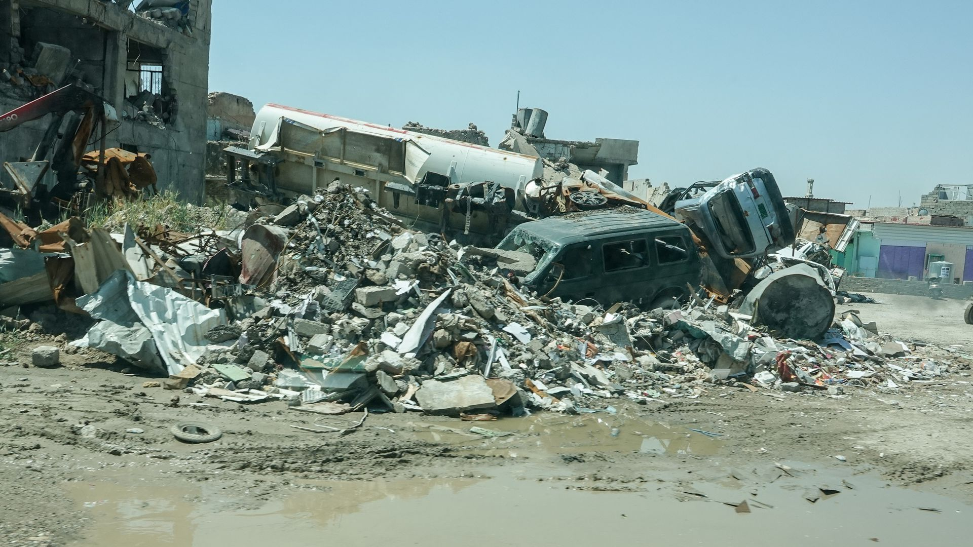 Houses and cars are that were destroyed by the Islamic State litter the city with debris.