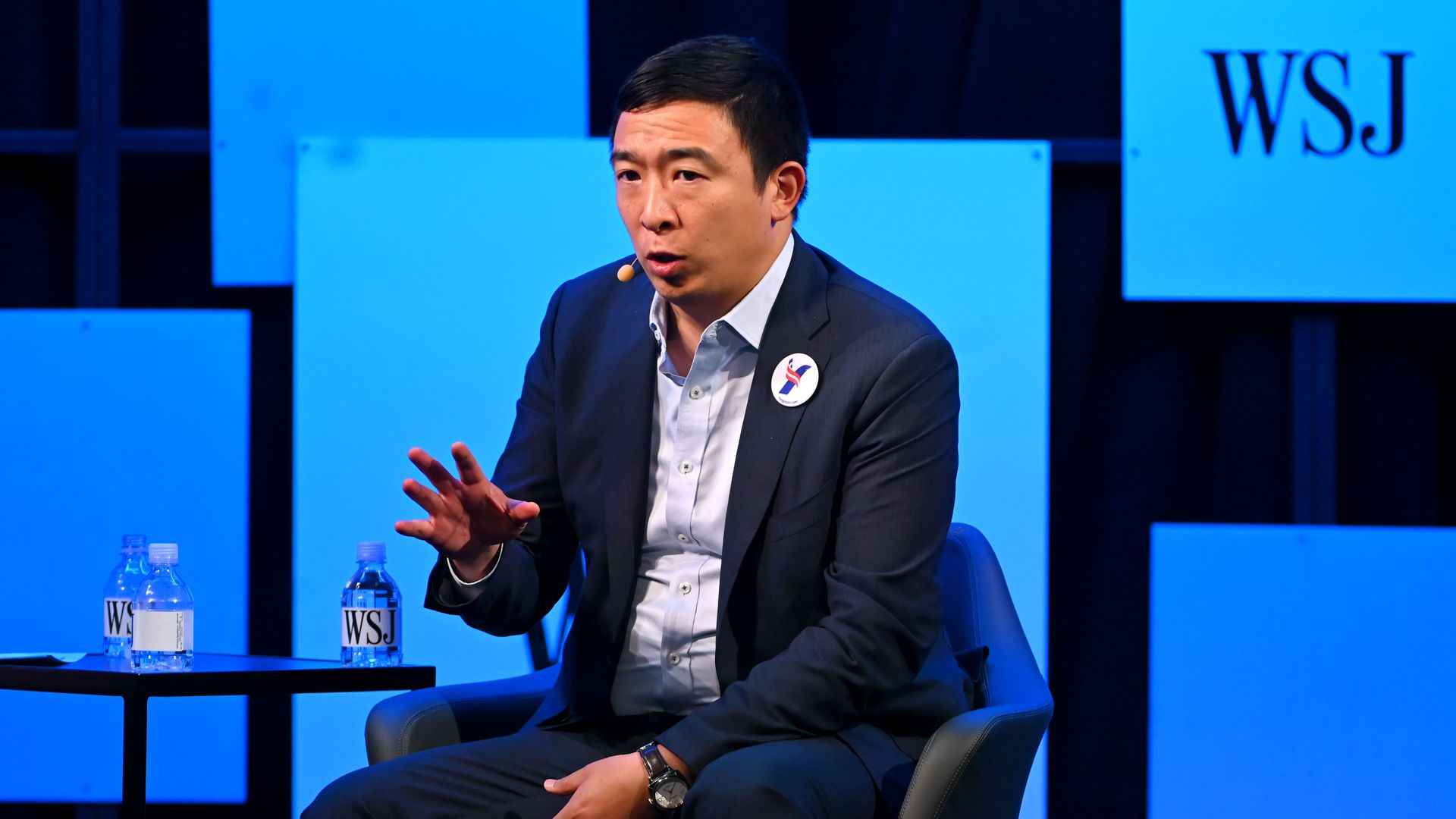 Andrew Yang sitting in a chair while extending his hand forward. he is wearing a suit, Yang button and in front of some Wall Street Journal graphics.