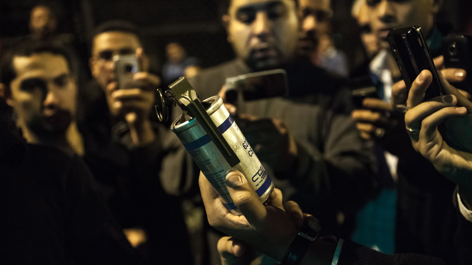 Protestor holding up a canister of tear gas