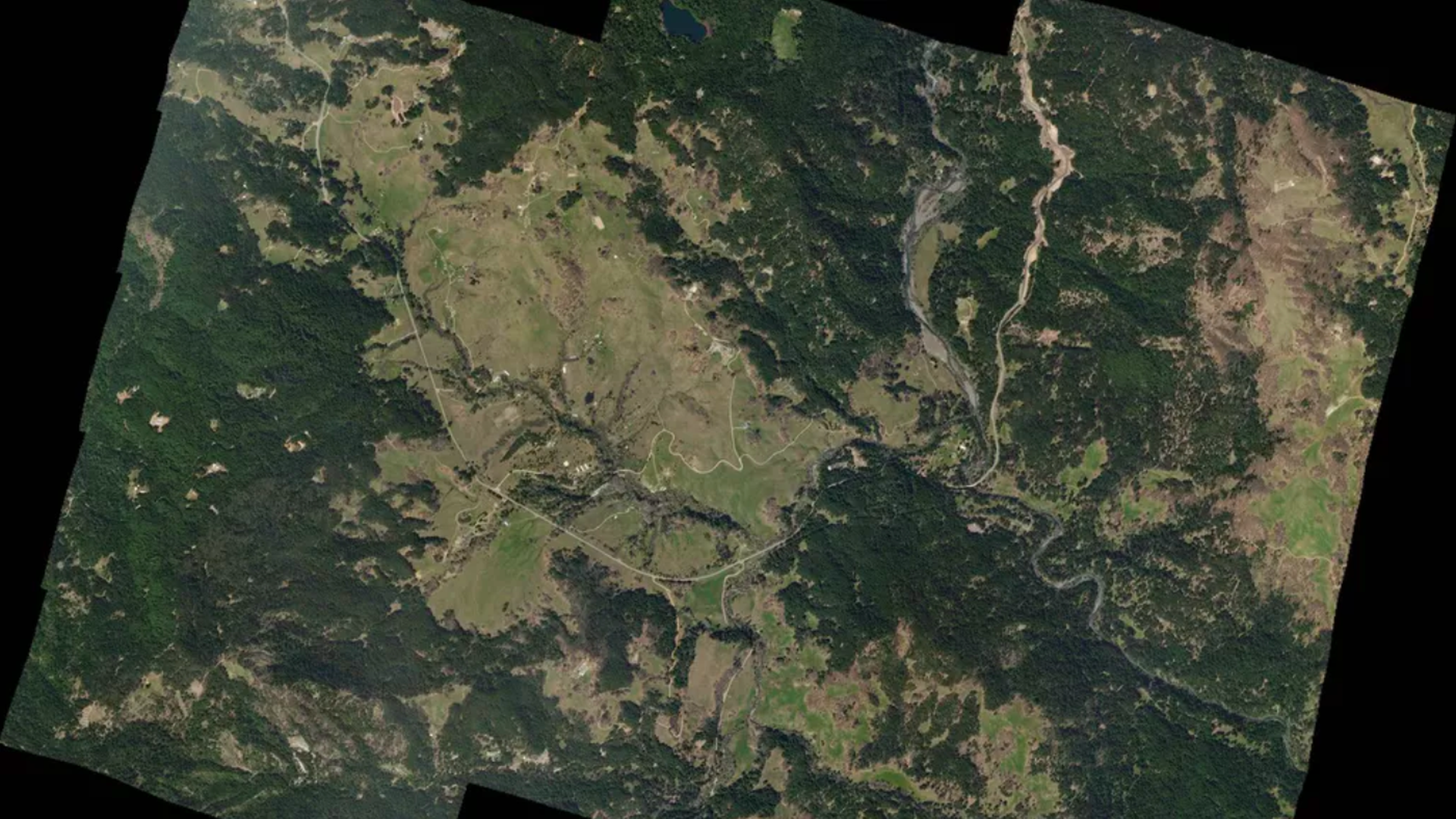 This image is a satellite image or birds eye view of a mountainous and forested region.