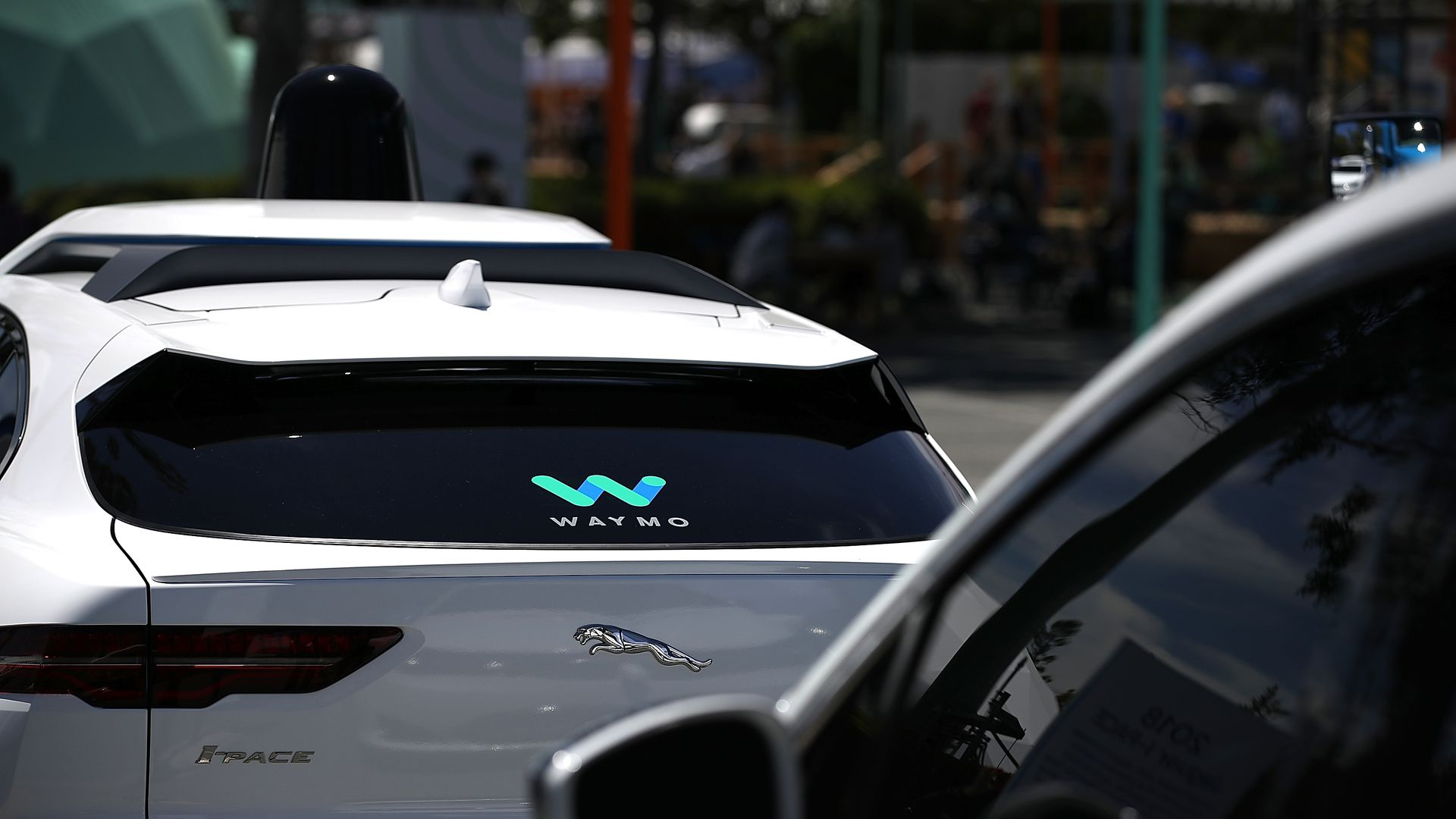 A self-driving car with the Waymo logo on its back windshield
