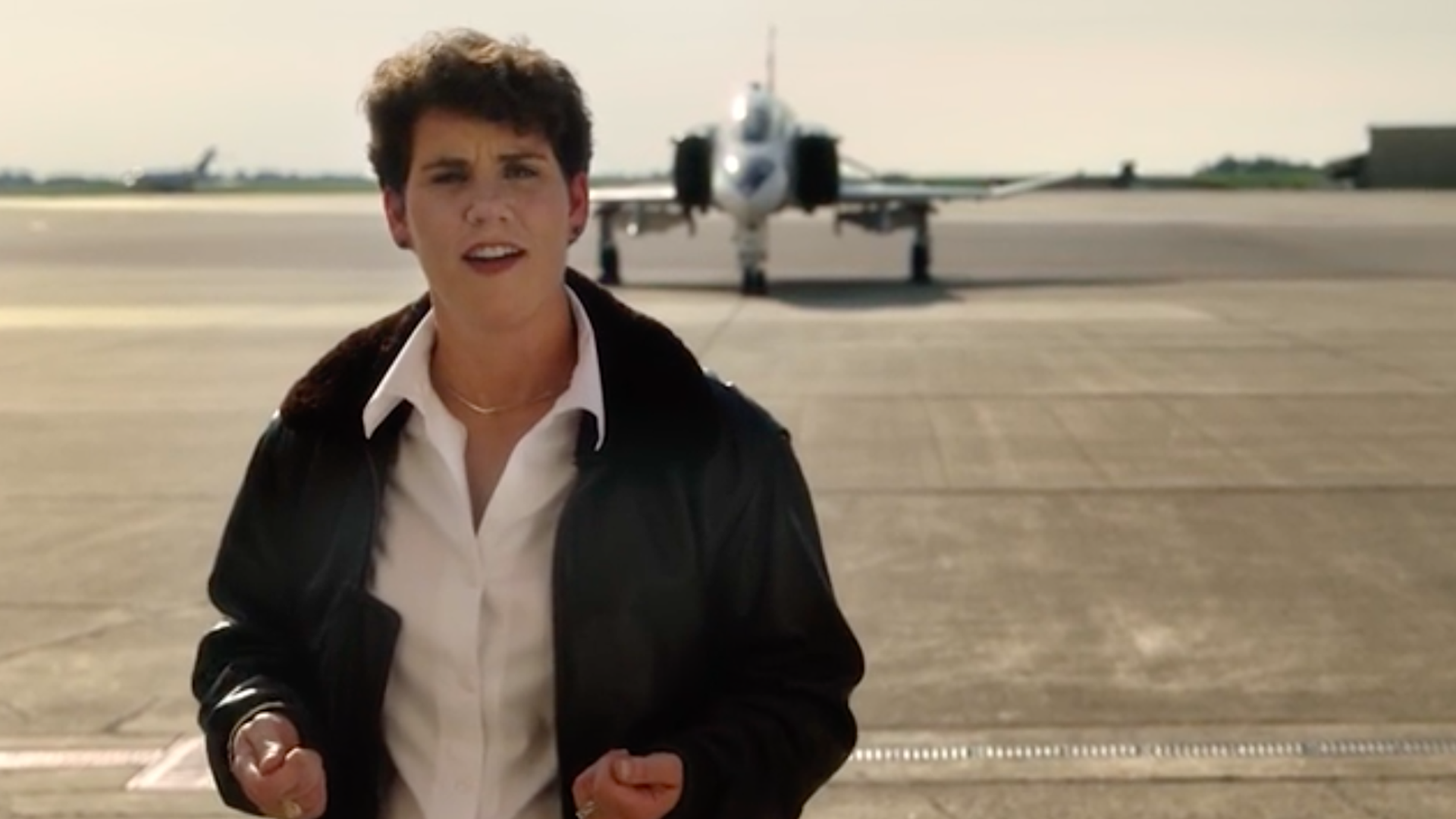 Amy McGrath standing in front of a fighter jet.