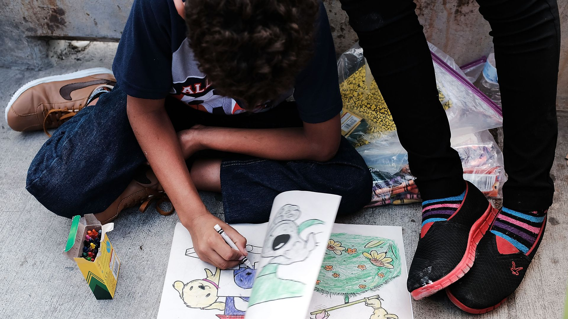 A Honduran child draws while waiting with his family after being denied entry into the Texas city of Brownsville which has become dependent on the daily crossing into and out of Mexico.