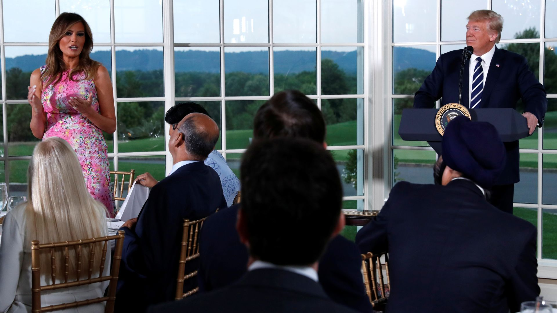 Donald Trump and Melania Trump are pictured here speaking in front of seated guests at a dinner, with several windows facing a golf course behind them.