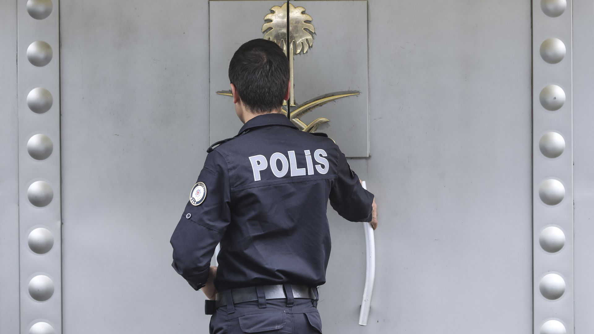 A Turkish police officer providing security enters the Saudi Arabia's consulate as they check papers of a man on October 12, 2018 in Istanbul, Turkey.