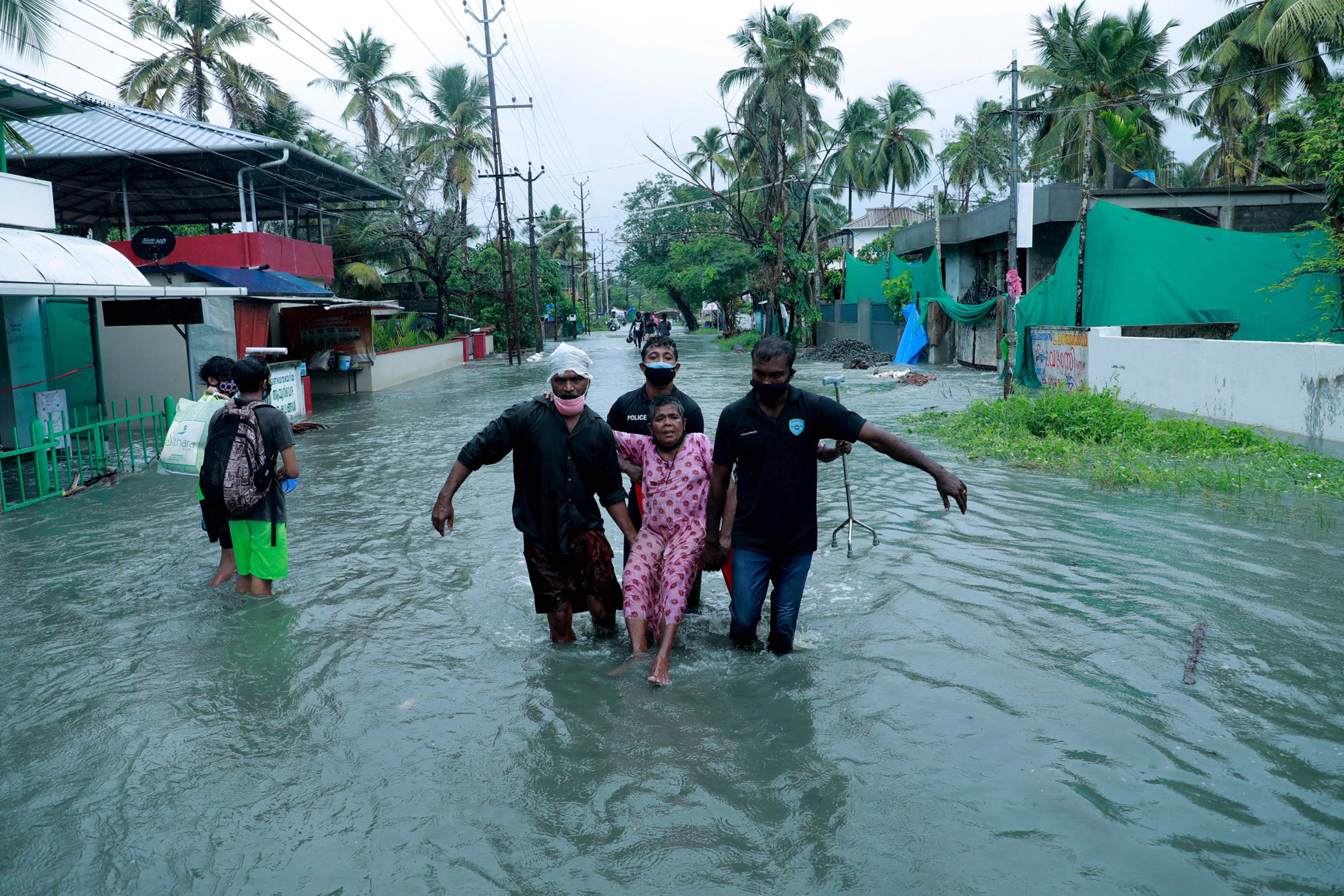 Police and rescue personnel evacuate a local resident through a flooded street in a coastal area after heavy rains under the influence of cyclone 'Tauktae' in Kochi on May 14