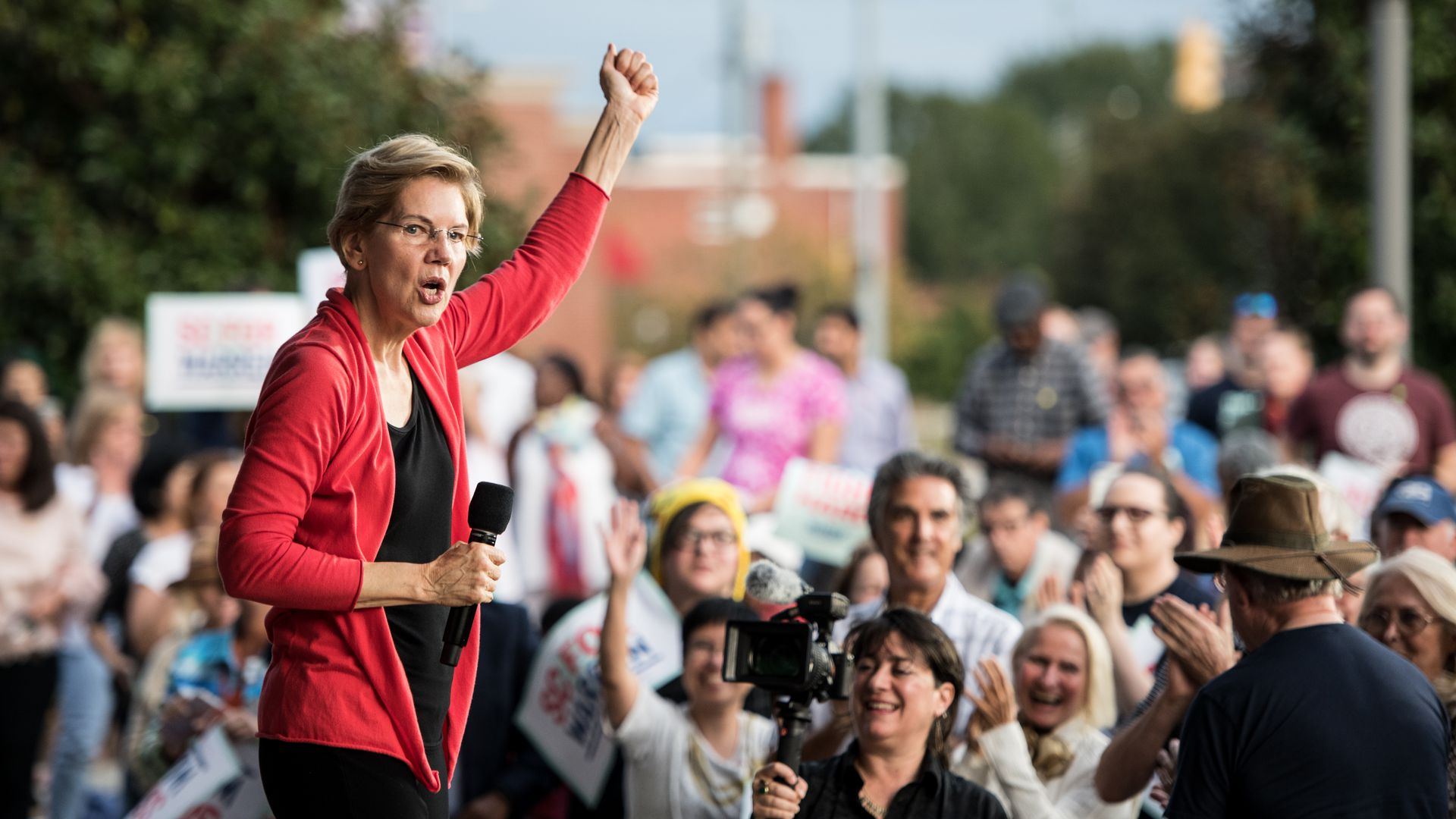 Elizabeth Warren, with her arm raised in a fist, speaks before a rally.
