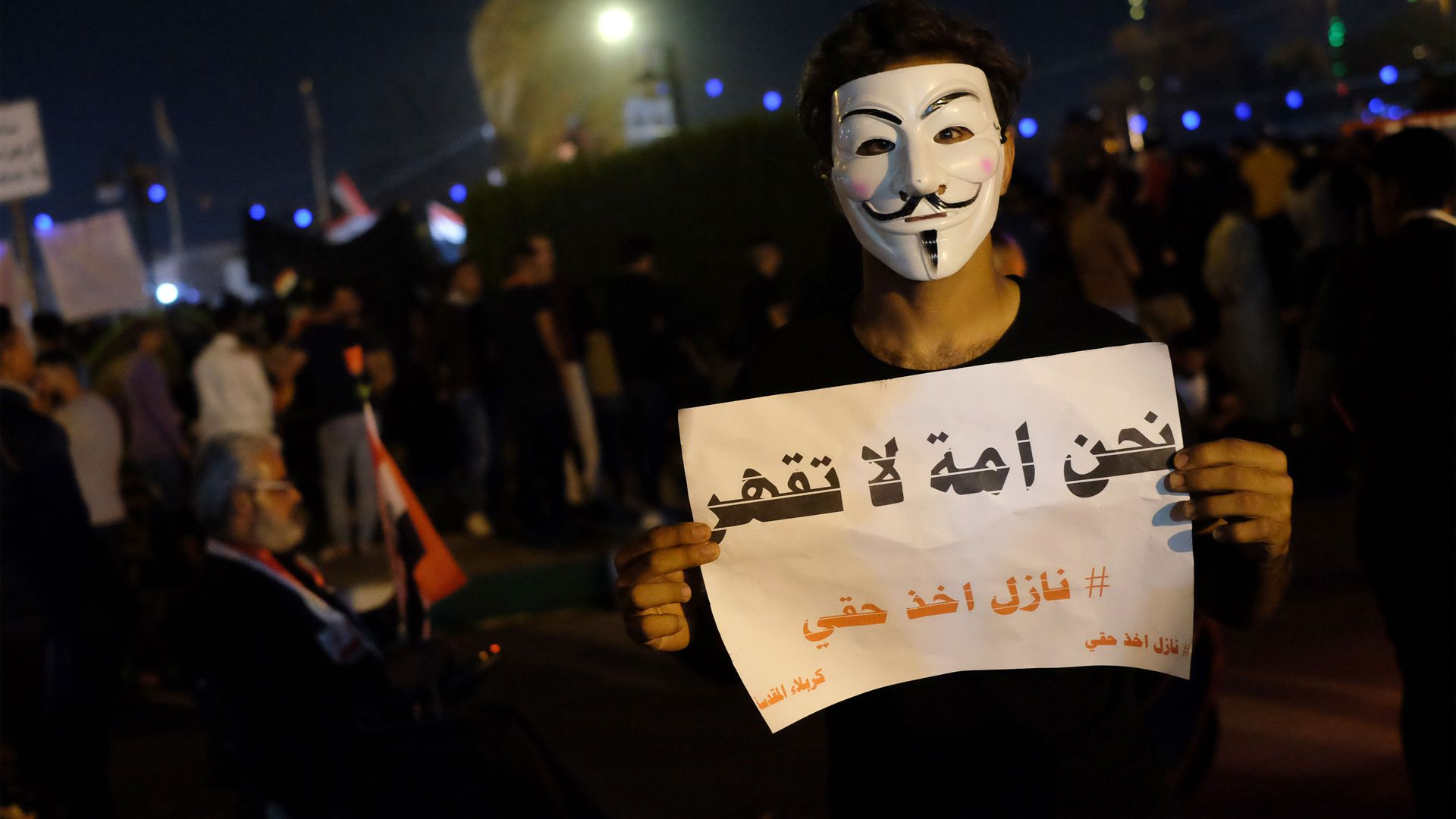 An Iraqi protester holds a placard during ongoing anti-government demonstrations in the Shiite shrine city of Karbala, south of Iraq's capital Baghdad, on November 1