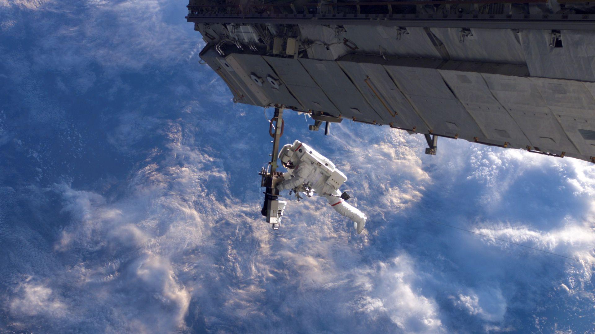 An astronaut on a spacewalk seen above the Earth