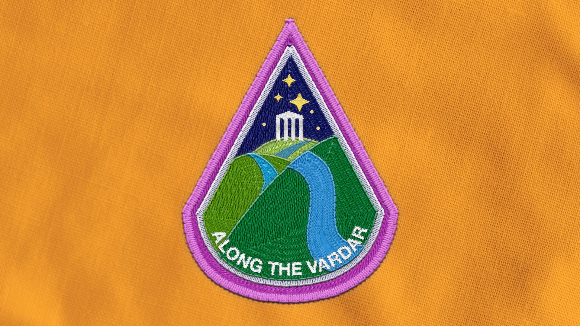"""Illustration of an astronaut badge depicting a river over rolling hills with a Grecian temple in the background, the words """"ALONG THE VARDAR"""" are on the badge."""
