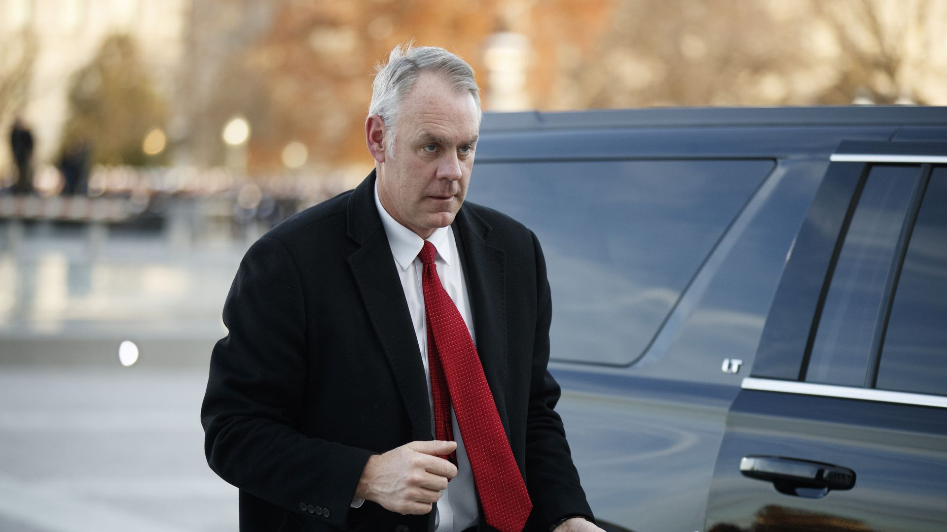 In this image, Ryan Zinke walks out of a black SUV with a red tie.