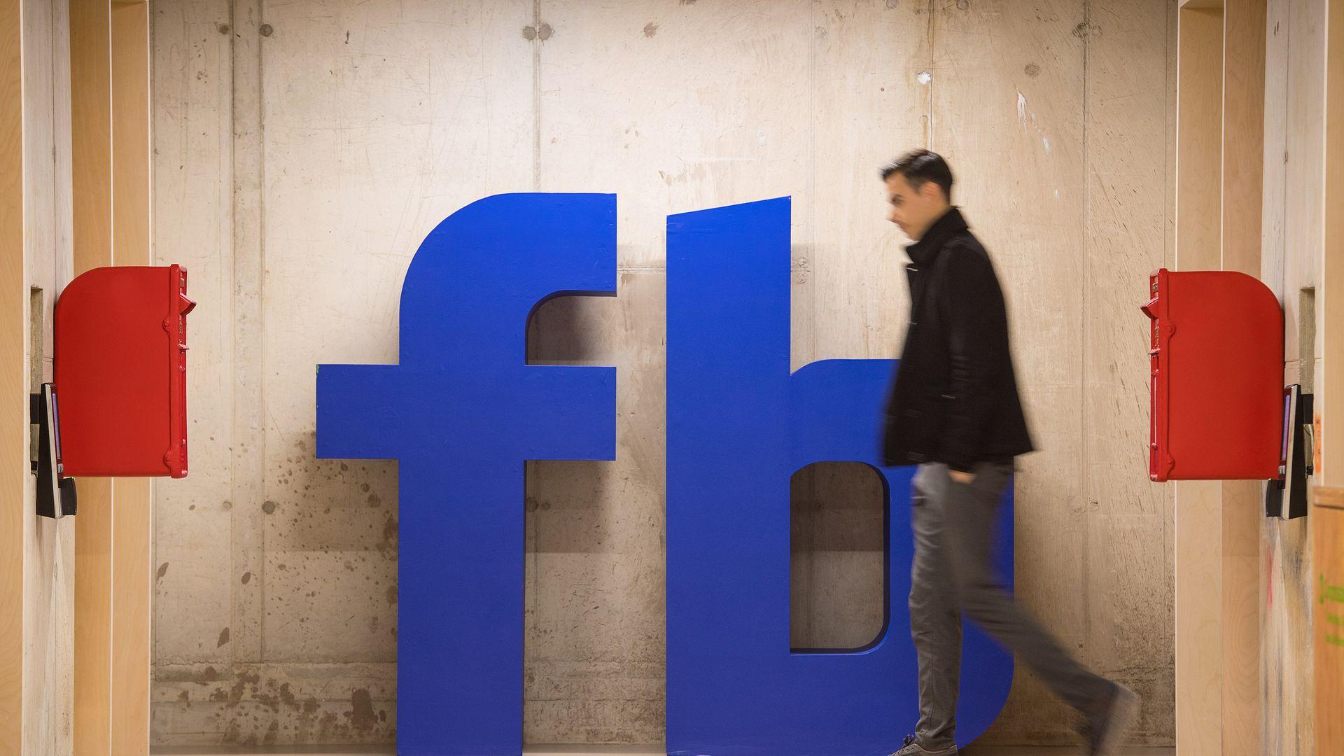 A man walks by a giant Facebook logo