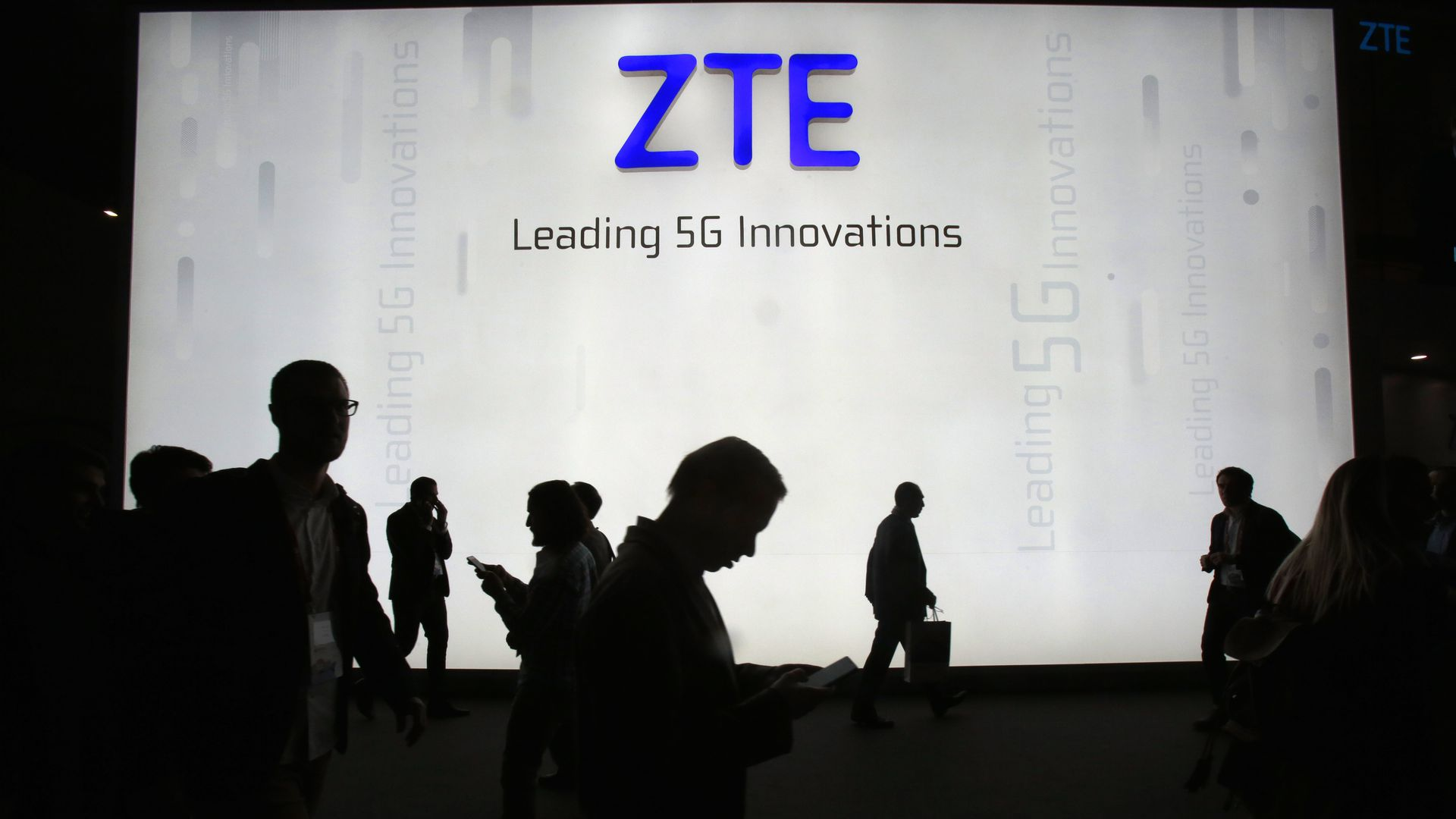Figures silhouetted in front of the ZTE logo