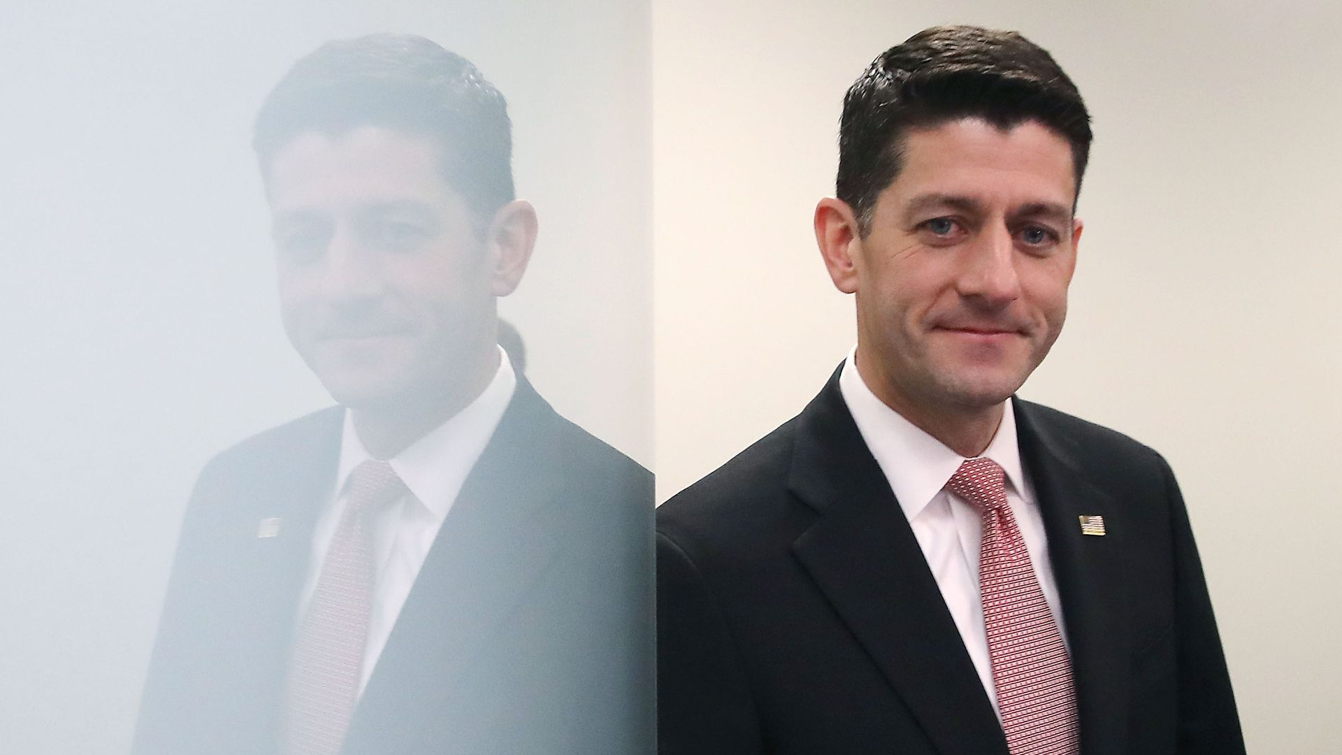 In this image, Paul Ryan leans against a reflective white wall while wearing a suit and red tie.