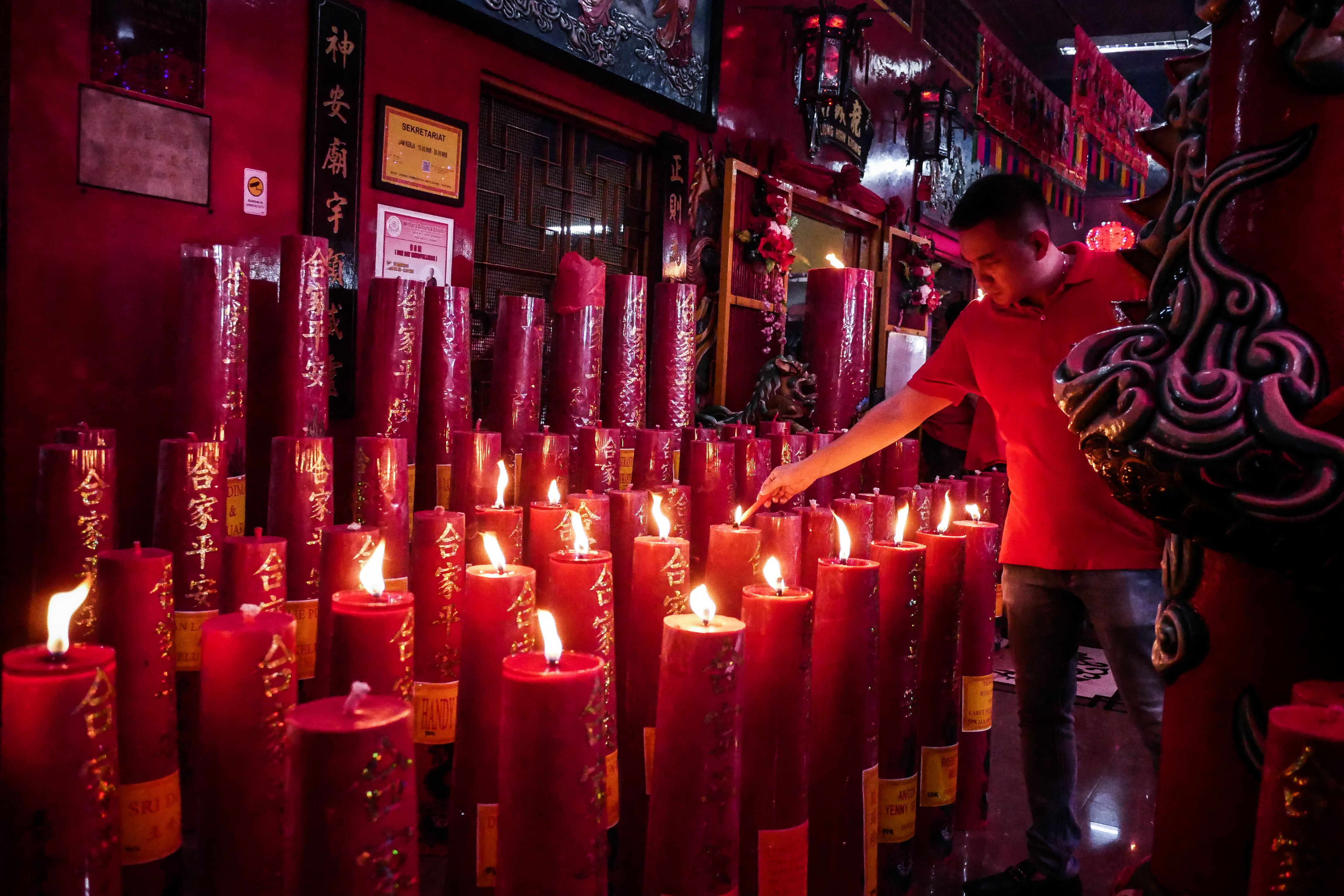 In this image, rows of red candles are lit