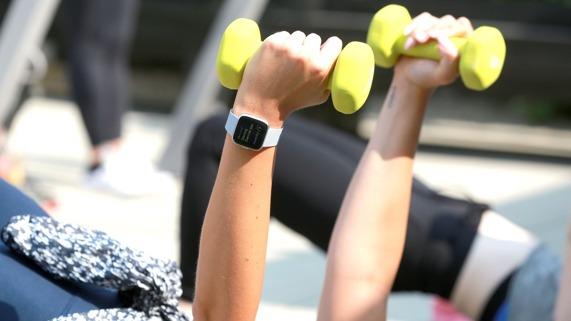 people holding dumbbells as they work out with a Fitbit fitness tracker