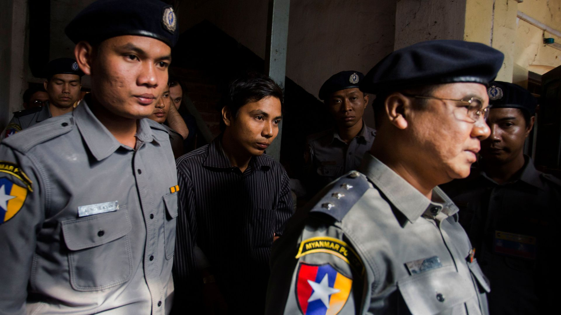 Reuters journalist Kyaw Soe Oo is escorted by Myanmar police outside the northern district court in Yangon