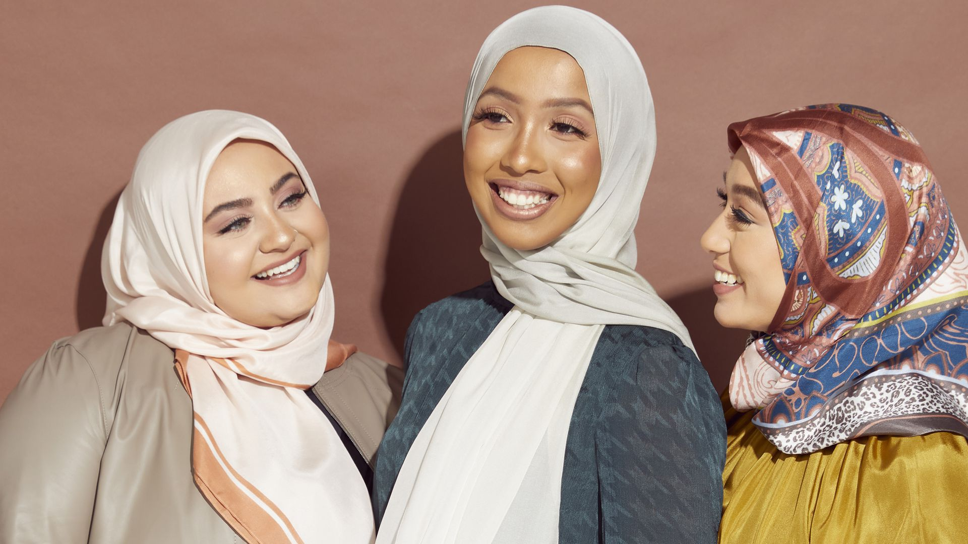 Three women wearing hijabs smile at one another.