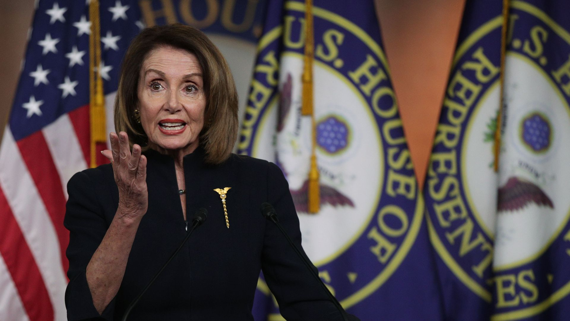 House Speaker Nancy Pelosi gestures with one hand.