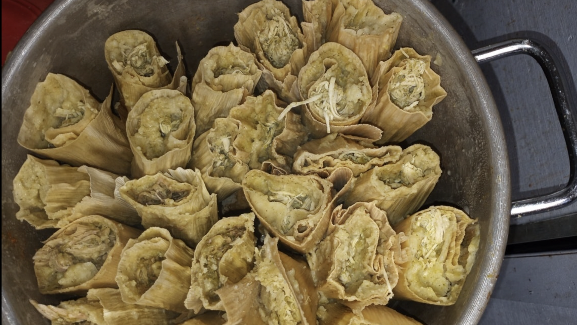 A pot filled with green tamales.