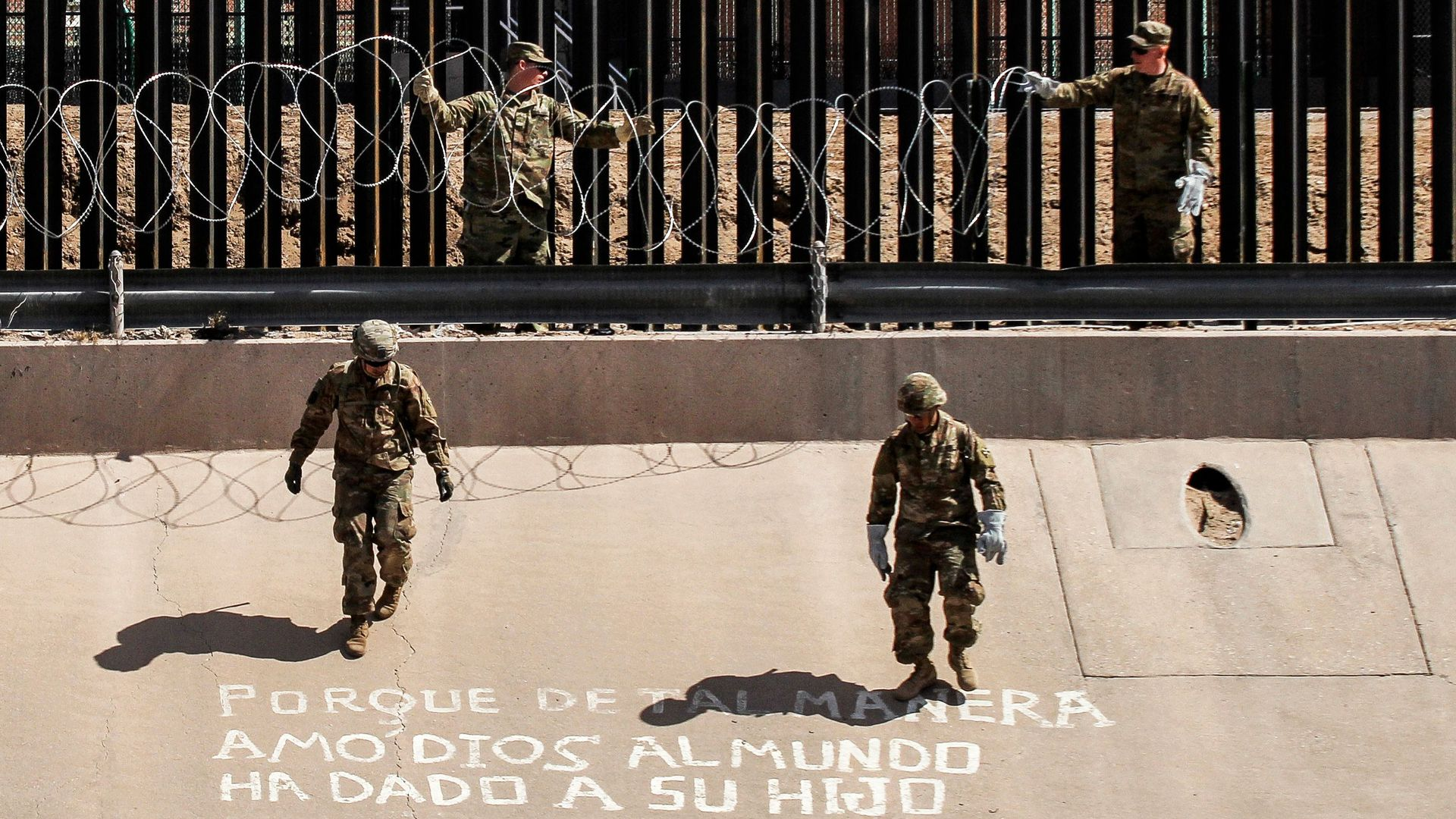 U.S. soldiers install barb wire by the US-Mexico border fence.