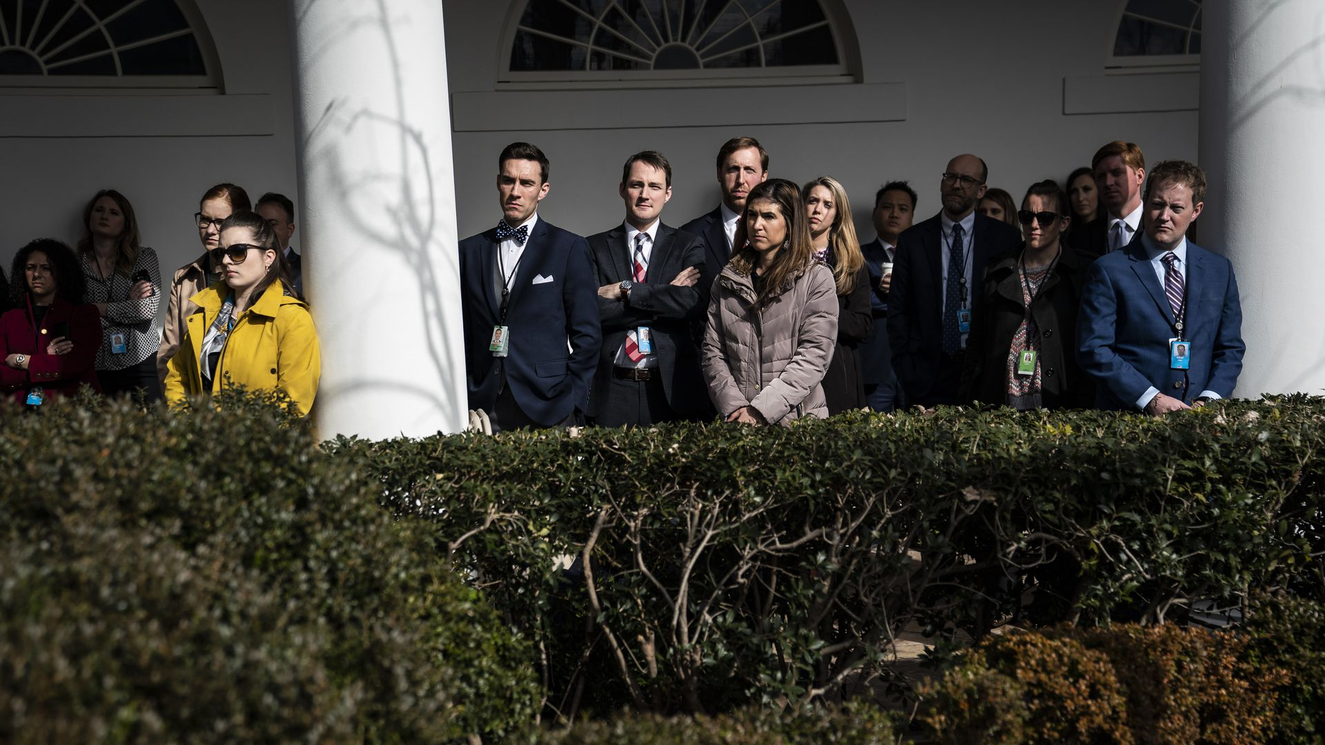 White House staff members watch as the president delivers a speech in the Rose Garden.