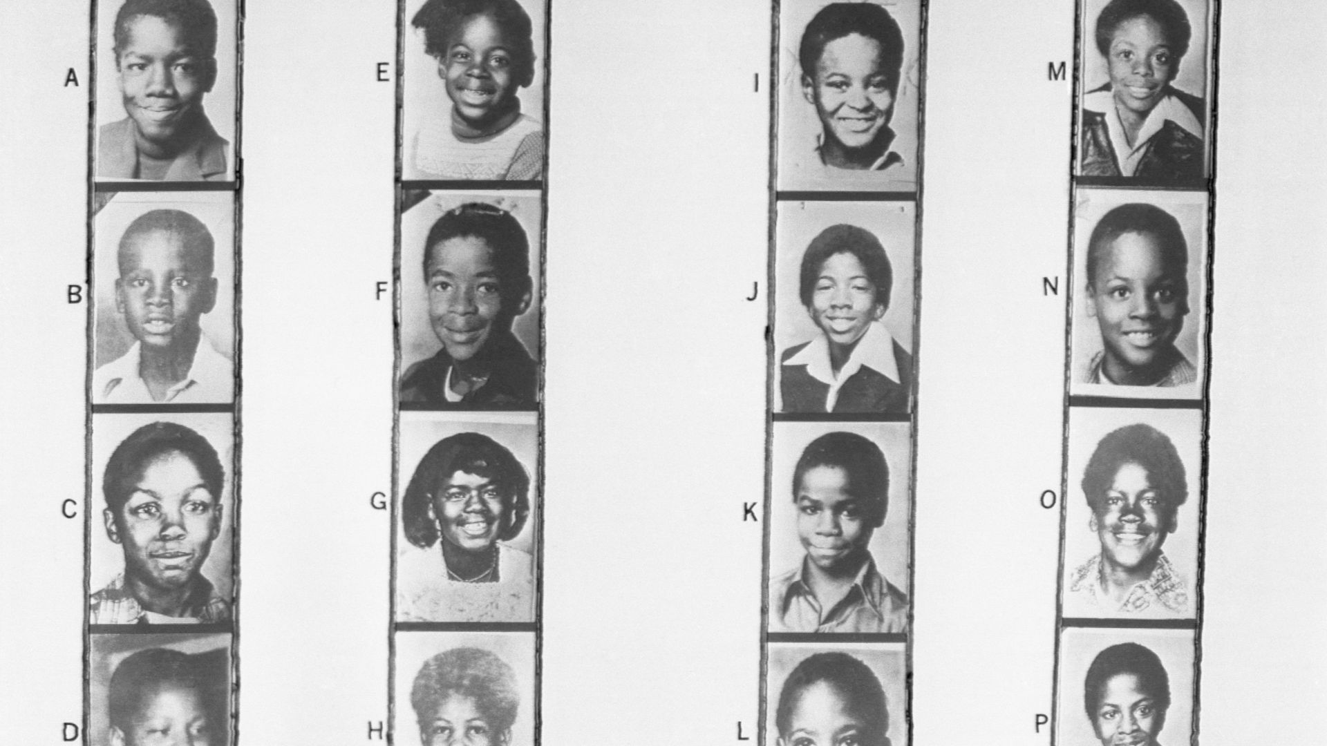 Rows of photographs of young Black children who were some of the victims in the Missing and Murdered Children cases in Atlanta