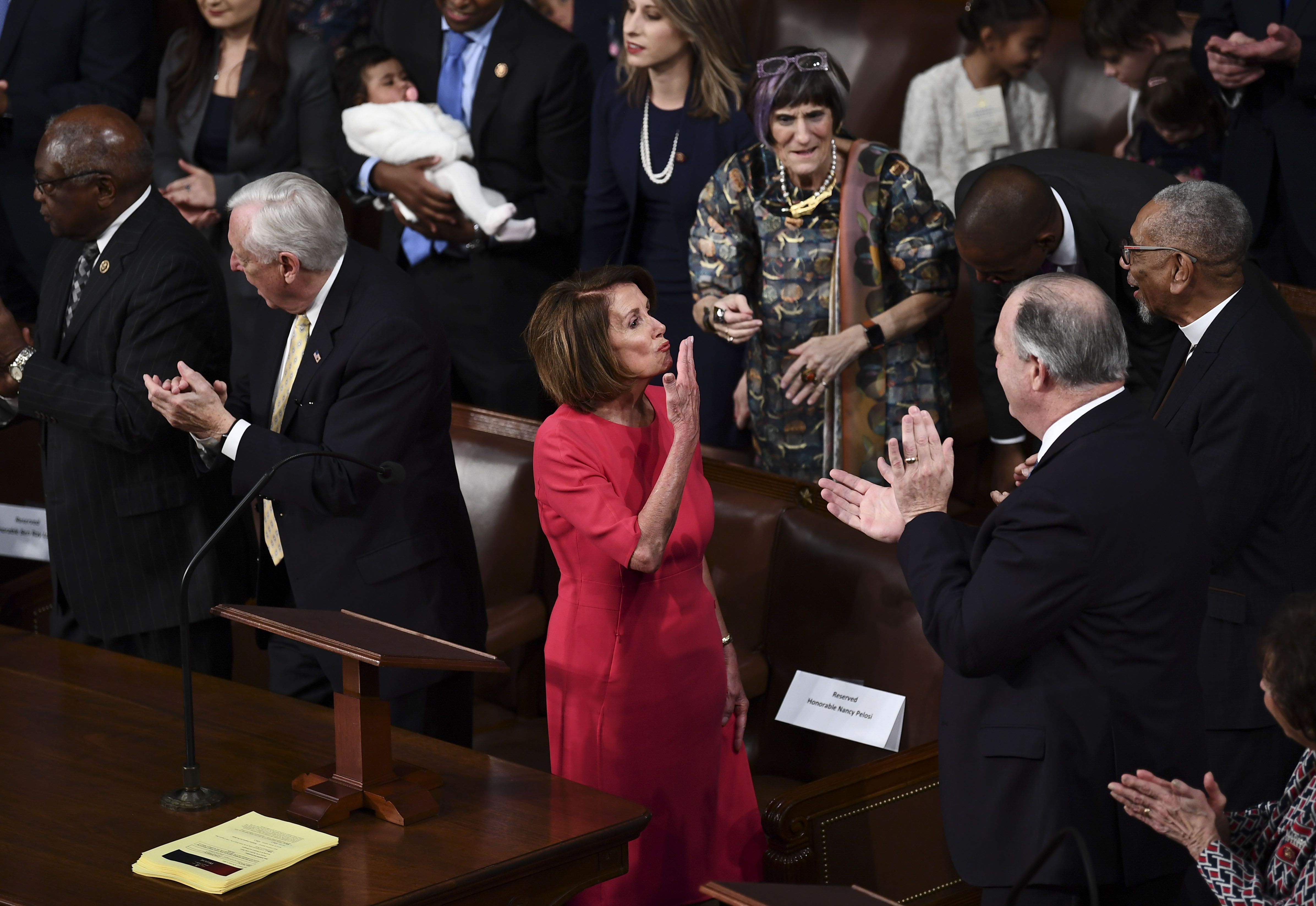 Nancy Pelosi blows a kiss on the House floor in pink dress.