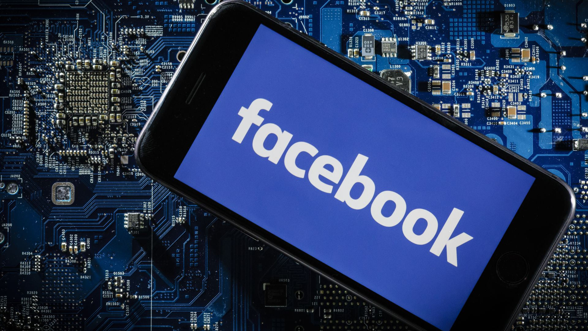 A phone displays the Facebook logo