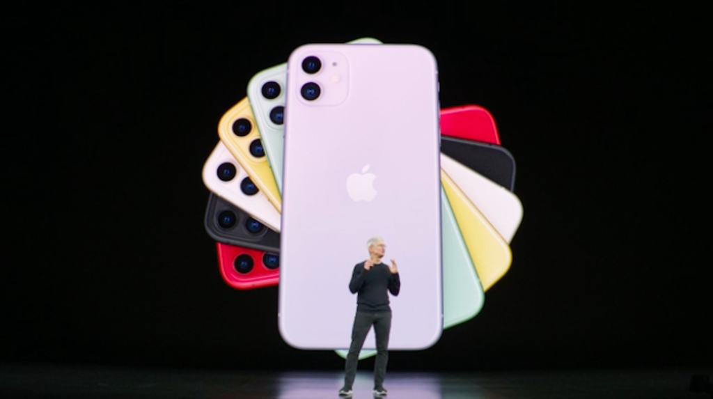 A screenshot of a photo of Apple CEO Tim Cook from the iPhone event with multiple iPhones in different colors behind him.