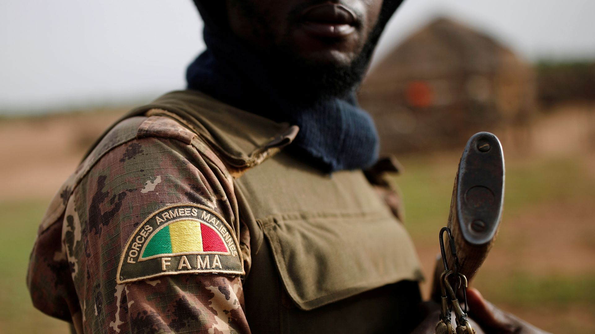 In this image, an armed soldier holds a gun and his sleeve is decorated with a patch that bears the Mali flag