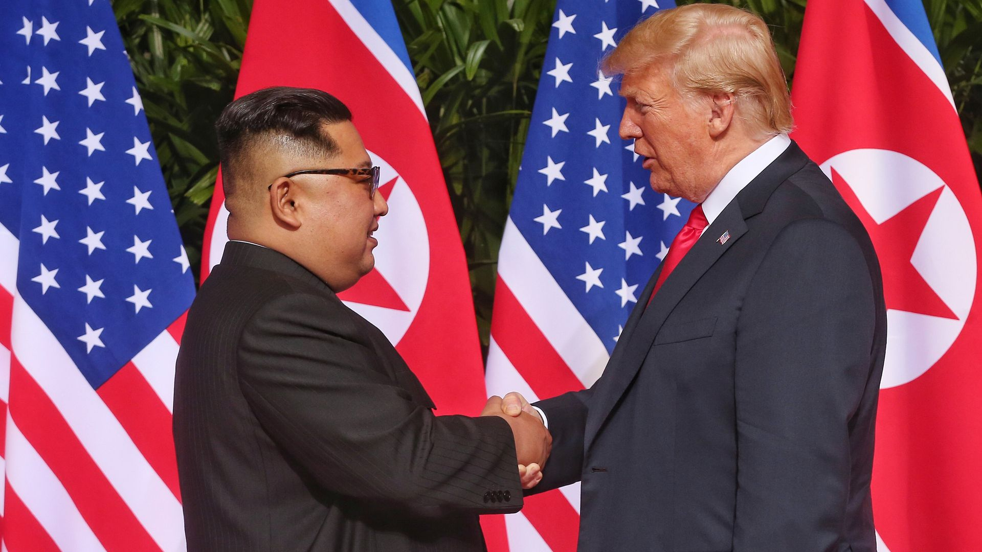 Donald Trump and Kim Jong-un shaking hands.